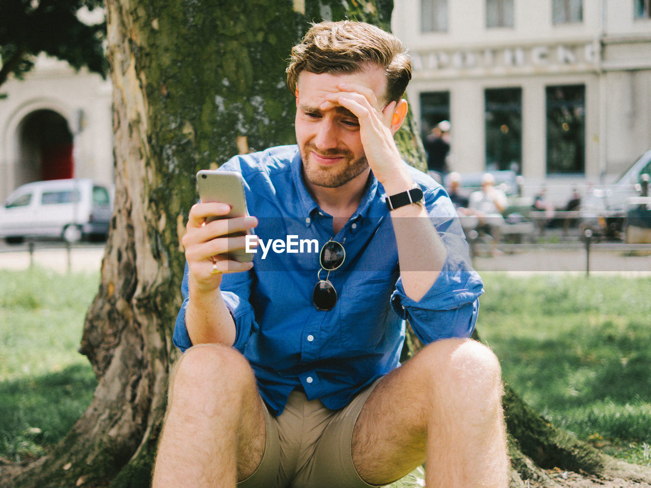 Disappointed Man Using Mobile Phone While Sitting By Tree