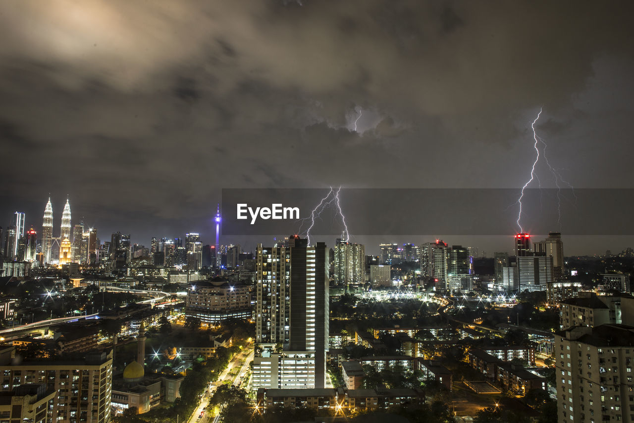 Lightning Over Illuminated Cityscape At Night
