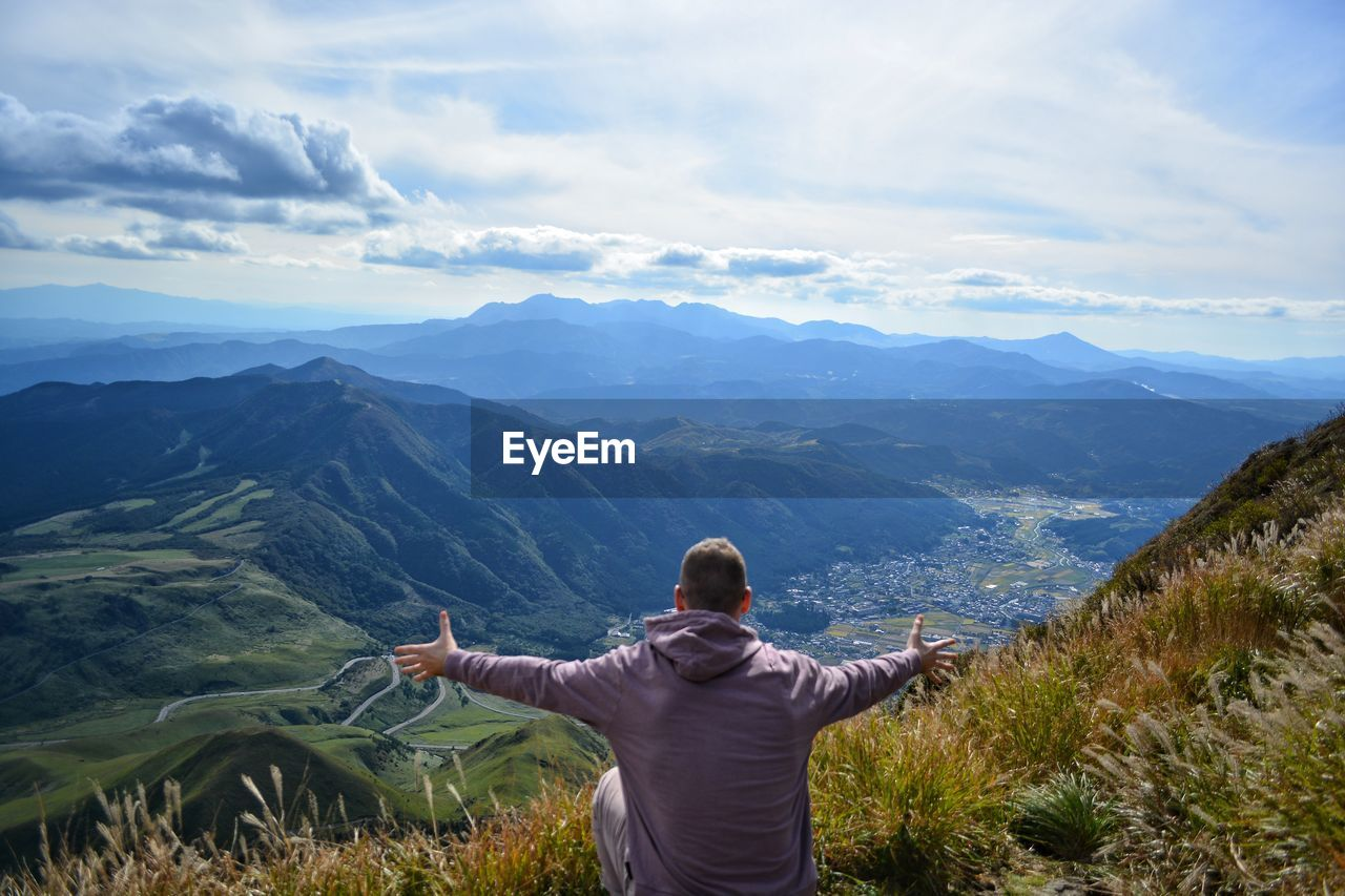 mountain, rear view, scenics - nature, beauty in nature, one person, sky, real people, leisure activity, tranquil scene, cloud - sky, non-urban scene, tranquility, lifestyles, mountain range, nature, human arm, idyllic, arms outstretched, environment, landscape, limb, outdoors, looking at view, arms raised