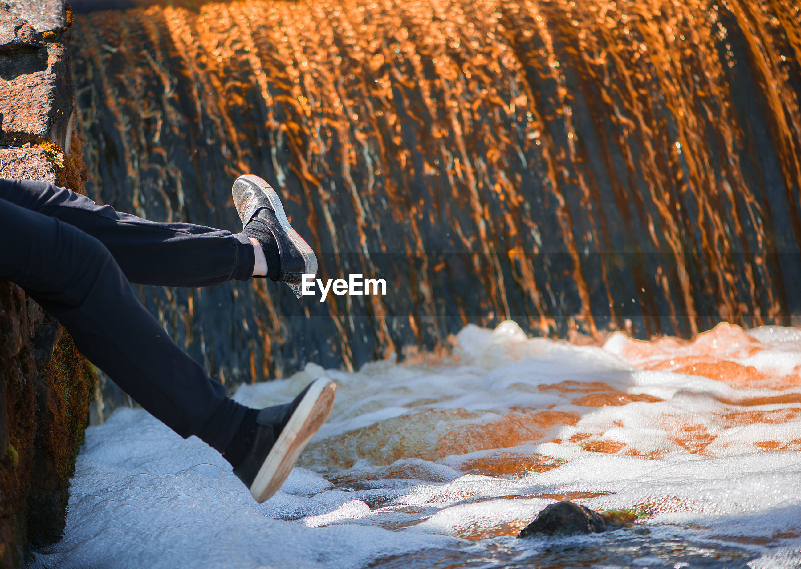 Low section of person sitting on rock over water