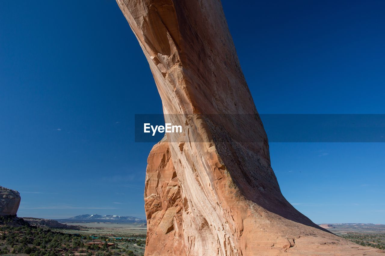 Low angle view of rock formation against blue sky at arches national park