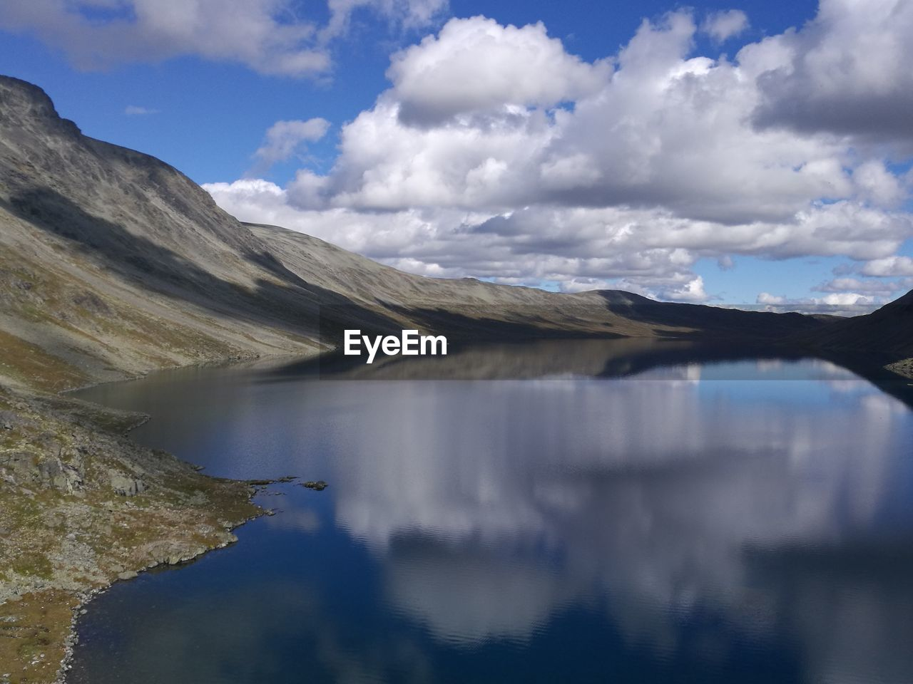 Scenic Shot Of Reflection Of Clouds In Calm Lake