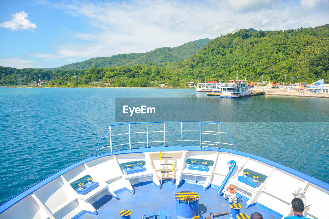 water, nautical vessel, transportation, mode of transportation, nature, sea, sky, cloud - sky, day, beauty in nature, mountain, scenics - nature, high angle view, ship, outdoors, architecture, incidental people, sunlight, passenger craft, cruise ship