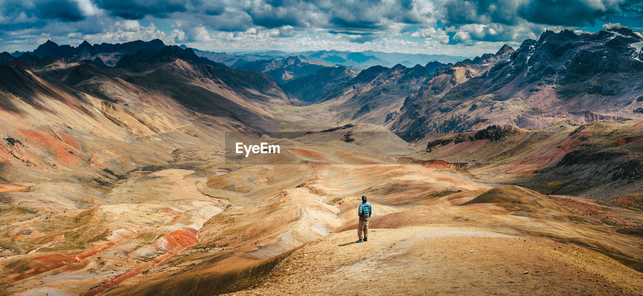 High angle view of man standing at altiplano against cloudy sky