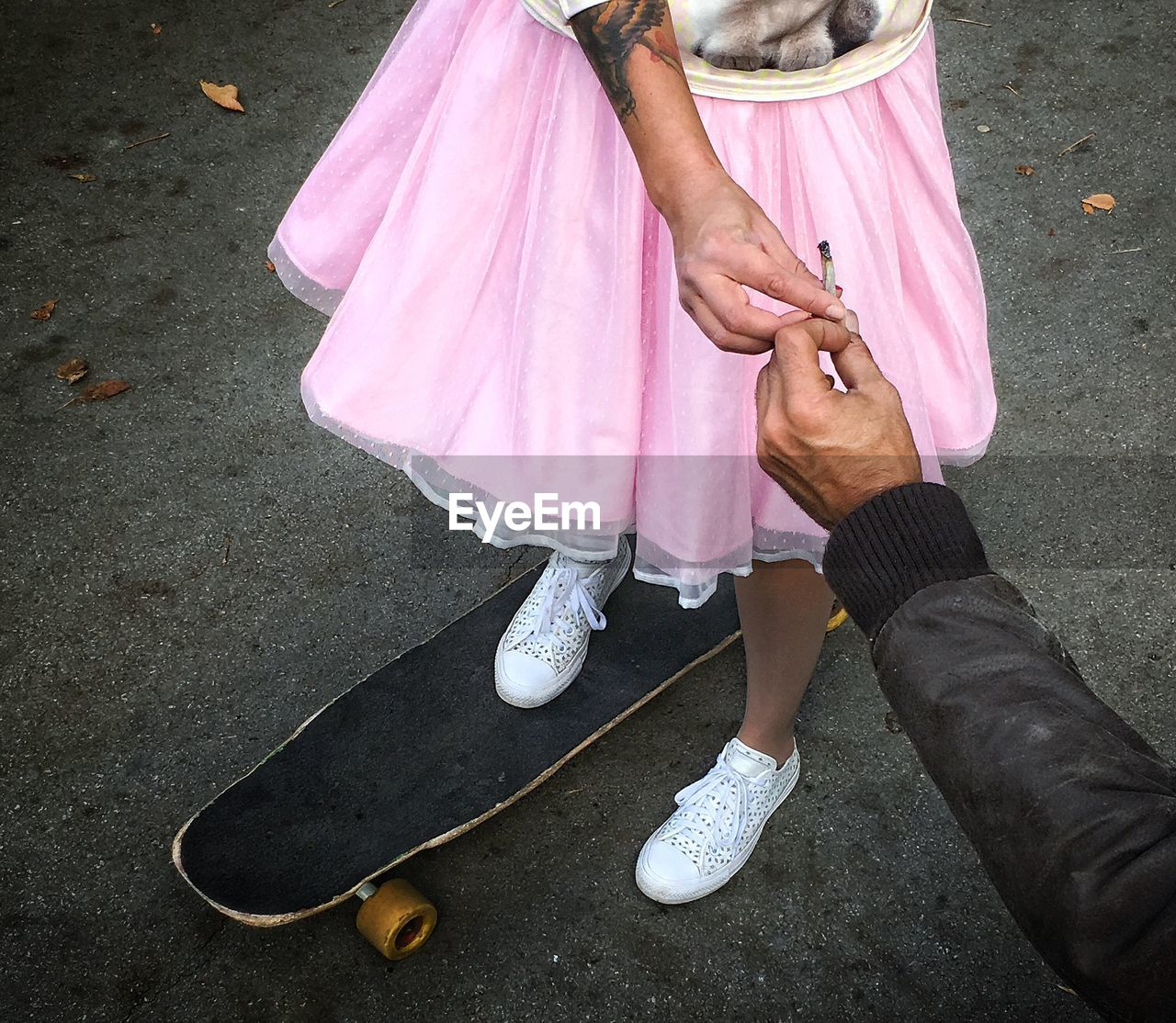 Low Section Of Woman On Skateboard Taking Joint From Man