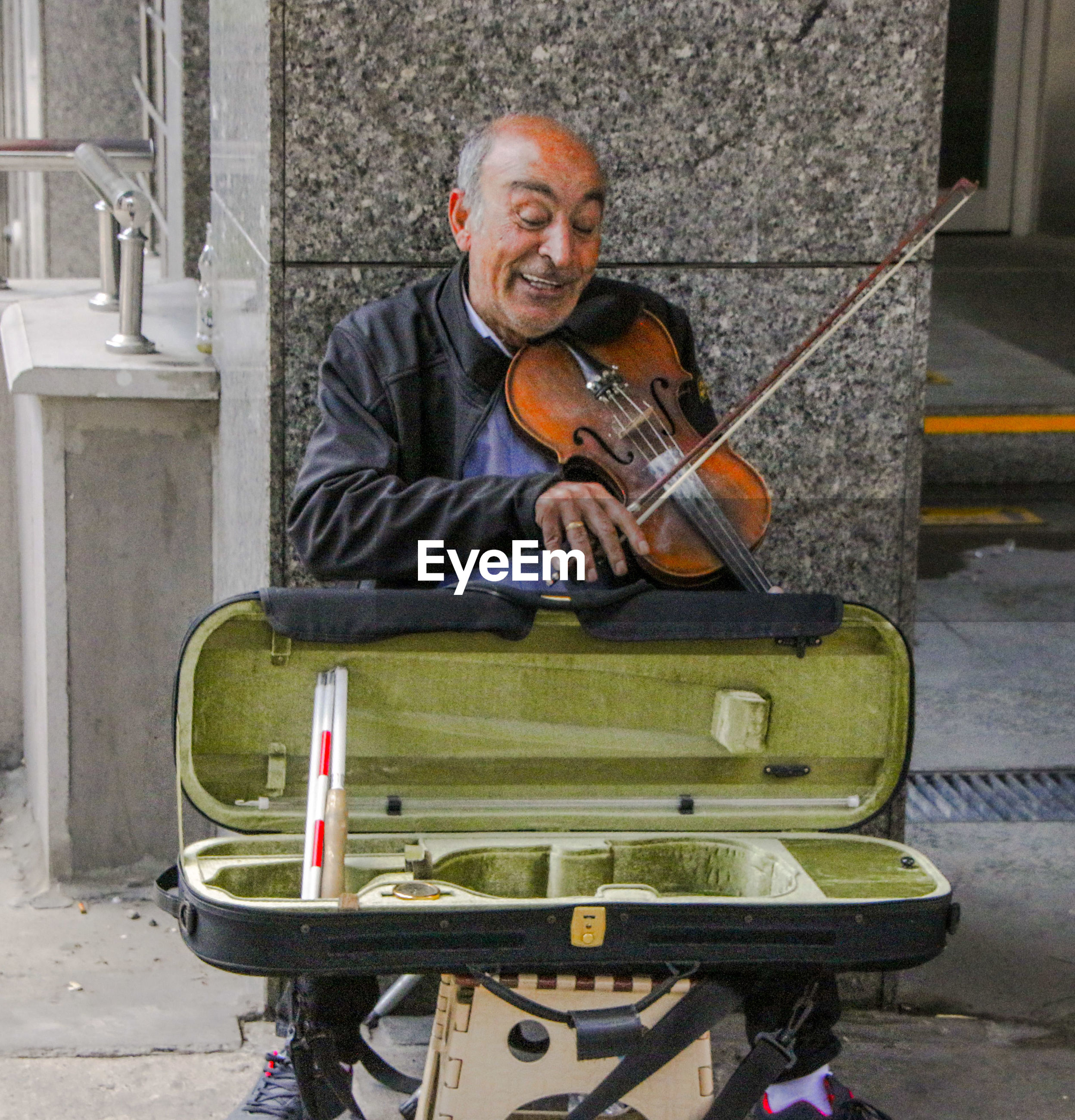 Smiling musician playing violin on street against wall