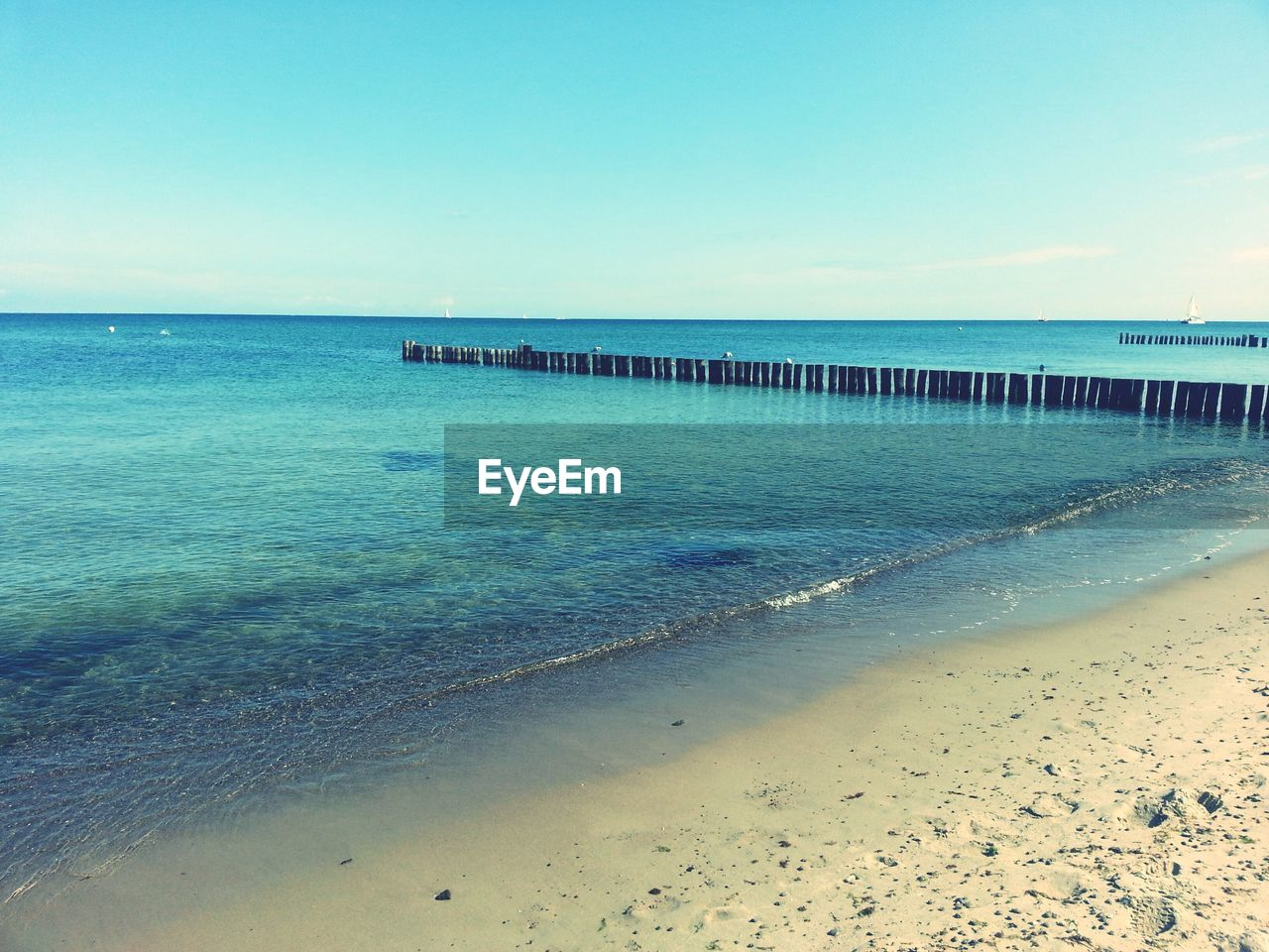 Row Of Wooden Posts On Sea Against Blue Sky
