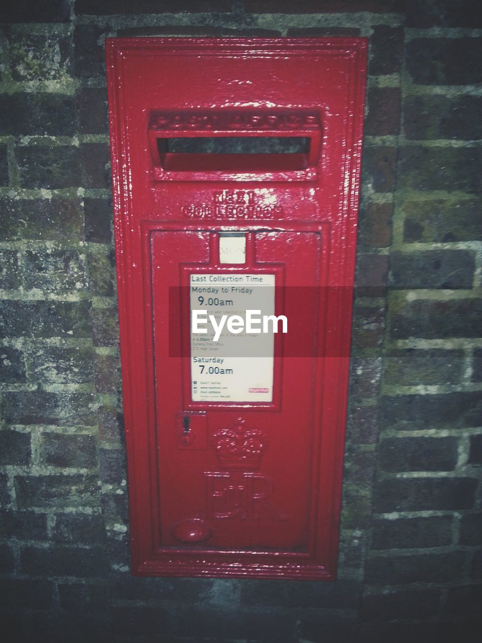 Red mailbox on wall at night