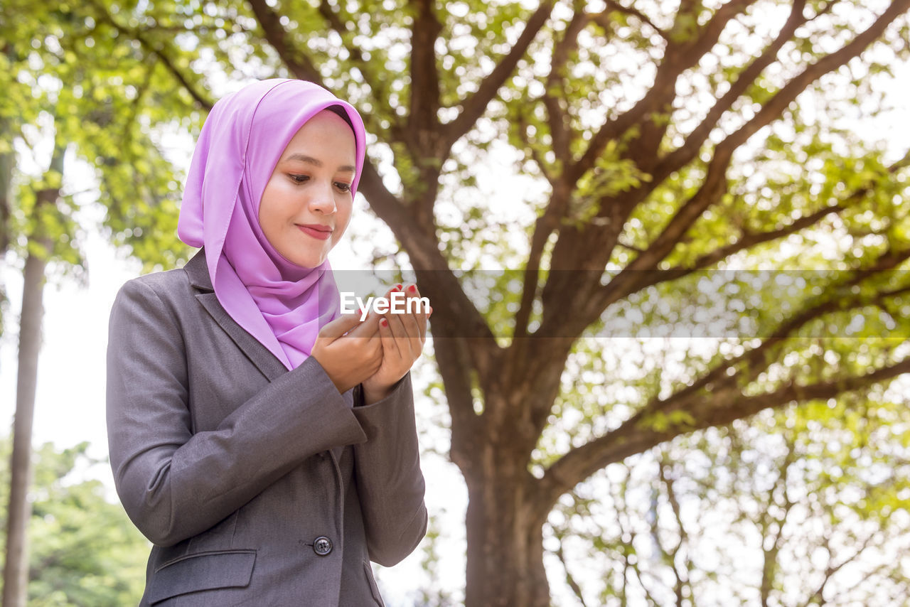 Smiling Young Woman Praying While Sitting In Park