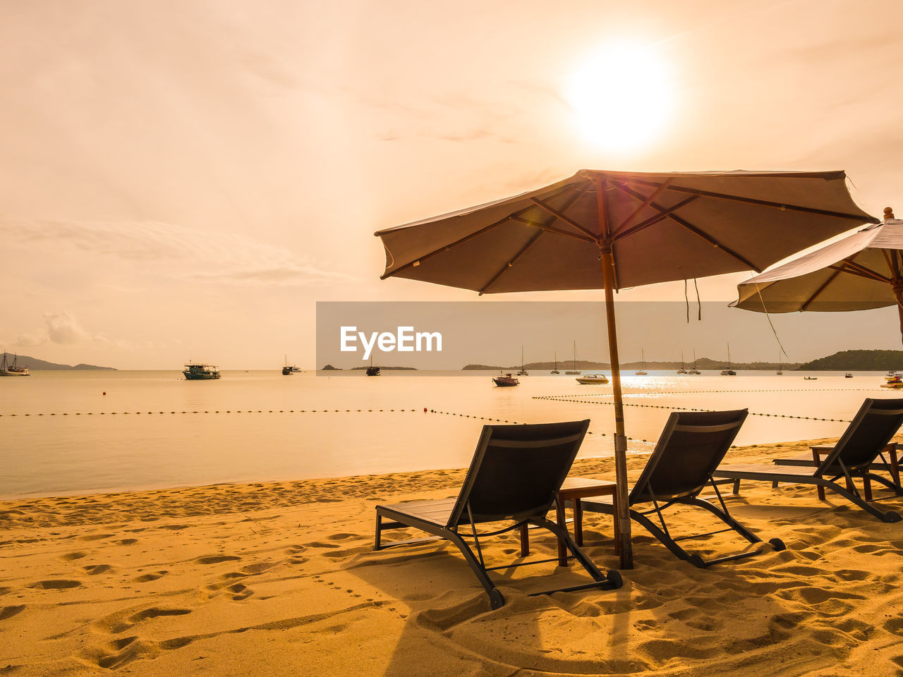 Deck Chairs Under Parasol At Beach Against Sky During Sunset