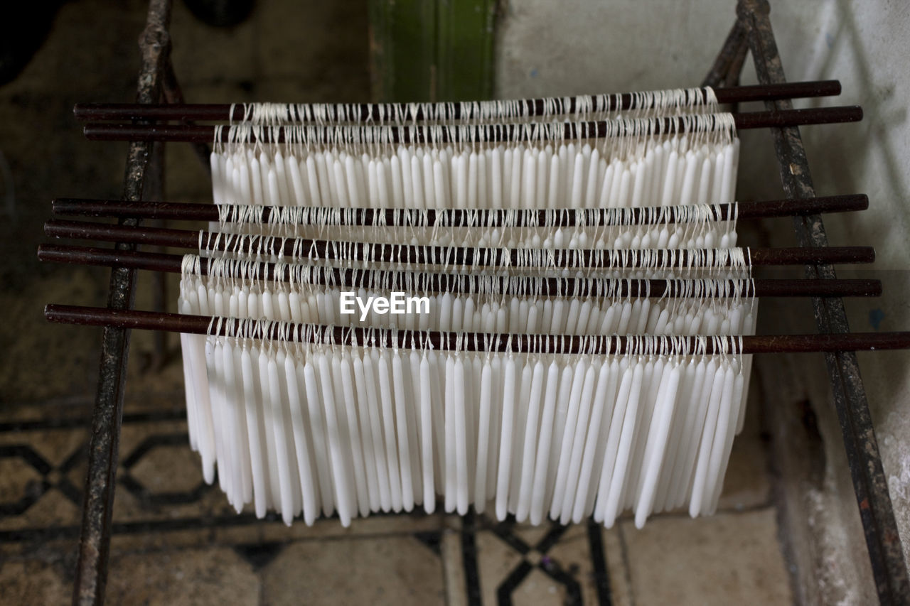 High angle view of candles tied to metallic rods