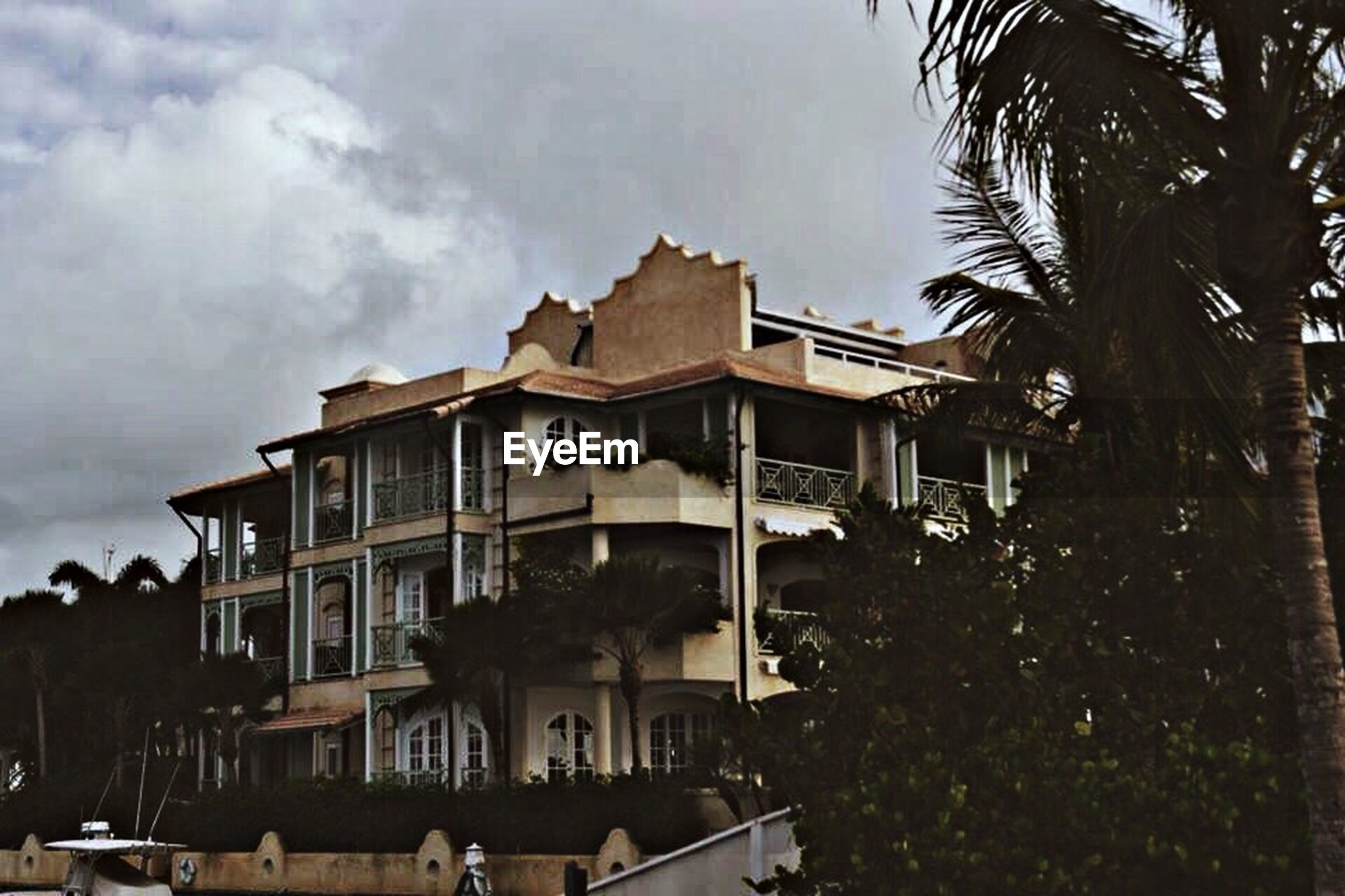 building exterior, architecture, built structure, sky, residential building, residential structure, house, window, tree, cloud - sky, city, residential district, roof, building, balcony, outdoors, day, cloud, palm tree, cloudy