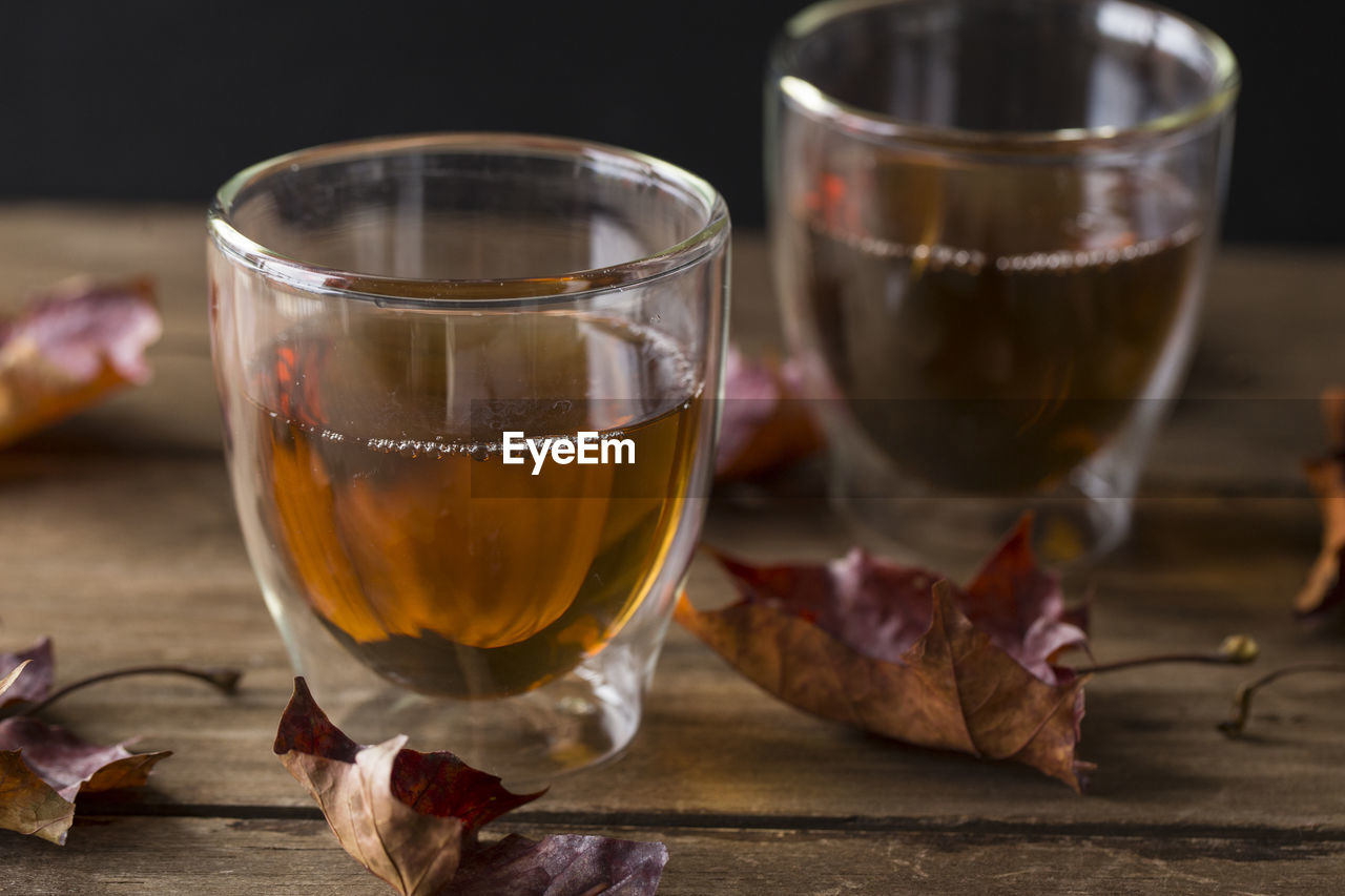 food and drink, table, freshness, refreshment, drink, indoors, alcohol, glass, close-up, no people, transparent, drinking glass, glass - material, household equipment, focus on foreground, still life, food, wood - material, tea, hot drink, red wine, tea cup