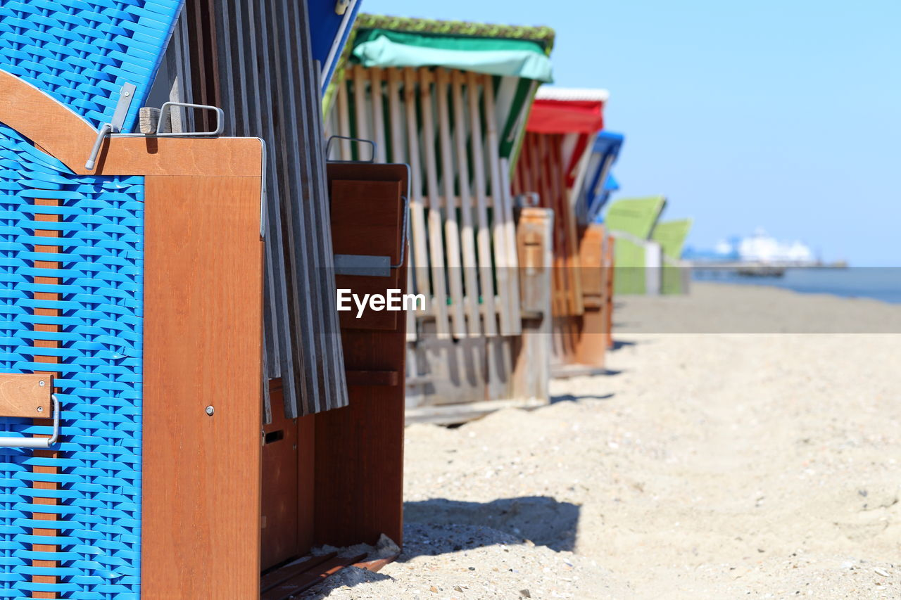 beach, focus on foreground, sunlight, day, land, in a row, no people, nature, sand, wood - material, shadow, built structure, hooded beach chair, architecture, outdoors, multi colored, blue, sky, selective focus, beach hut