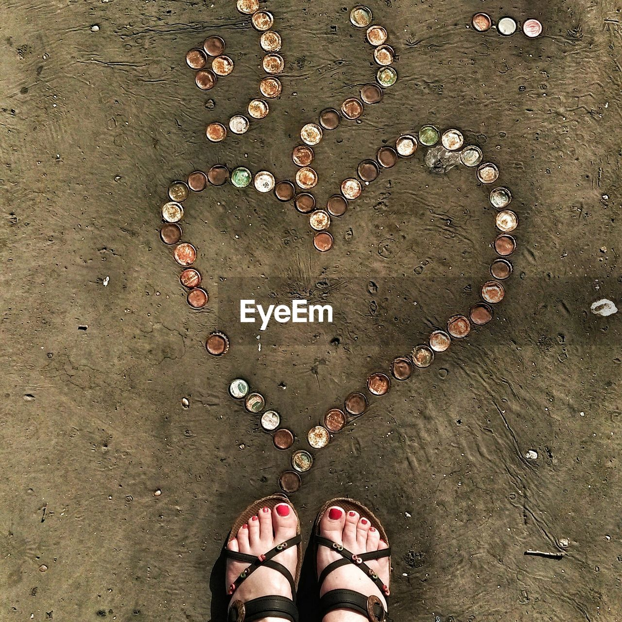 Directly above shot of womans feet near heart shape made with bottle caps