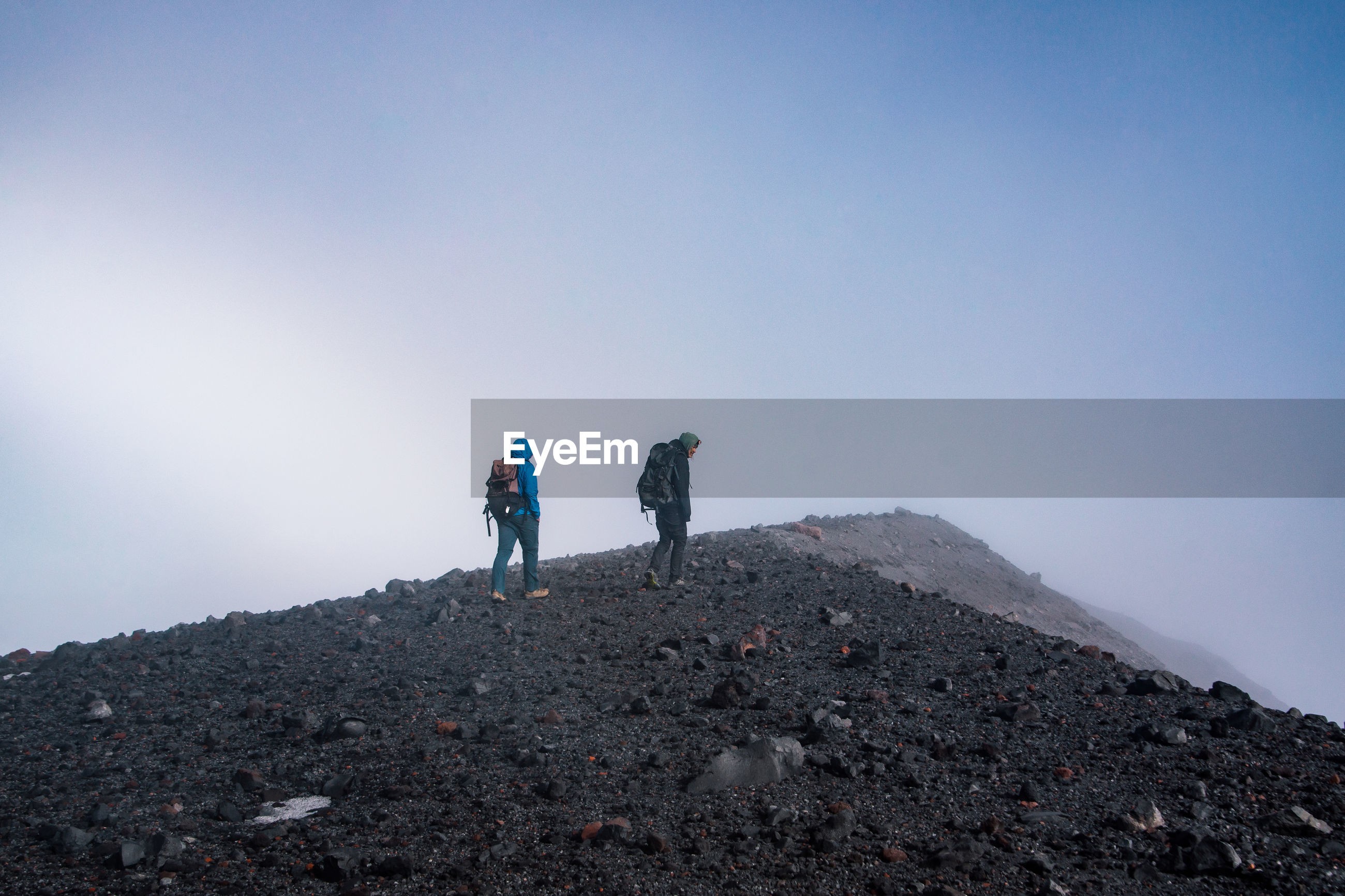 Male hikers hiking on mountain during winter