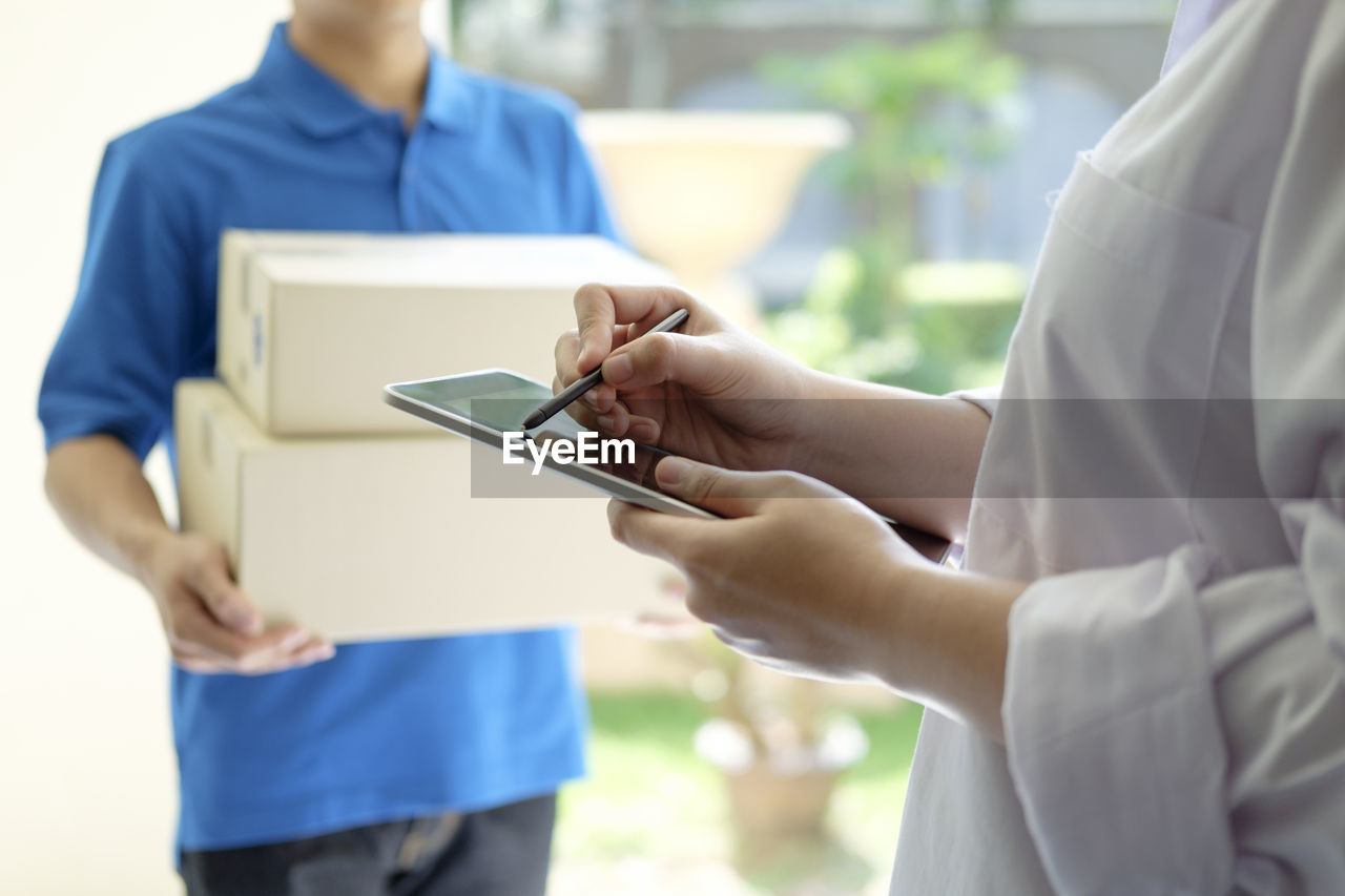 Midsection Of Woman Using Digital Tablet While Receiving Package
