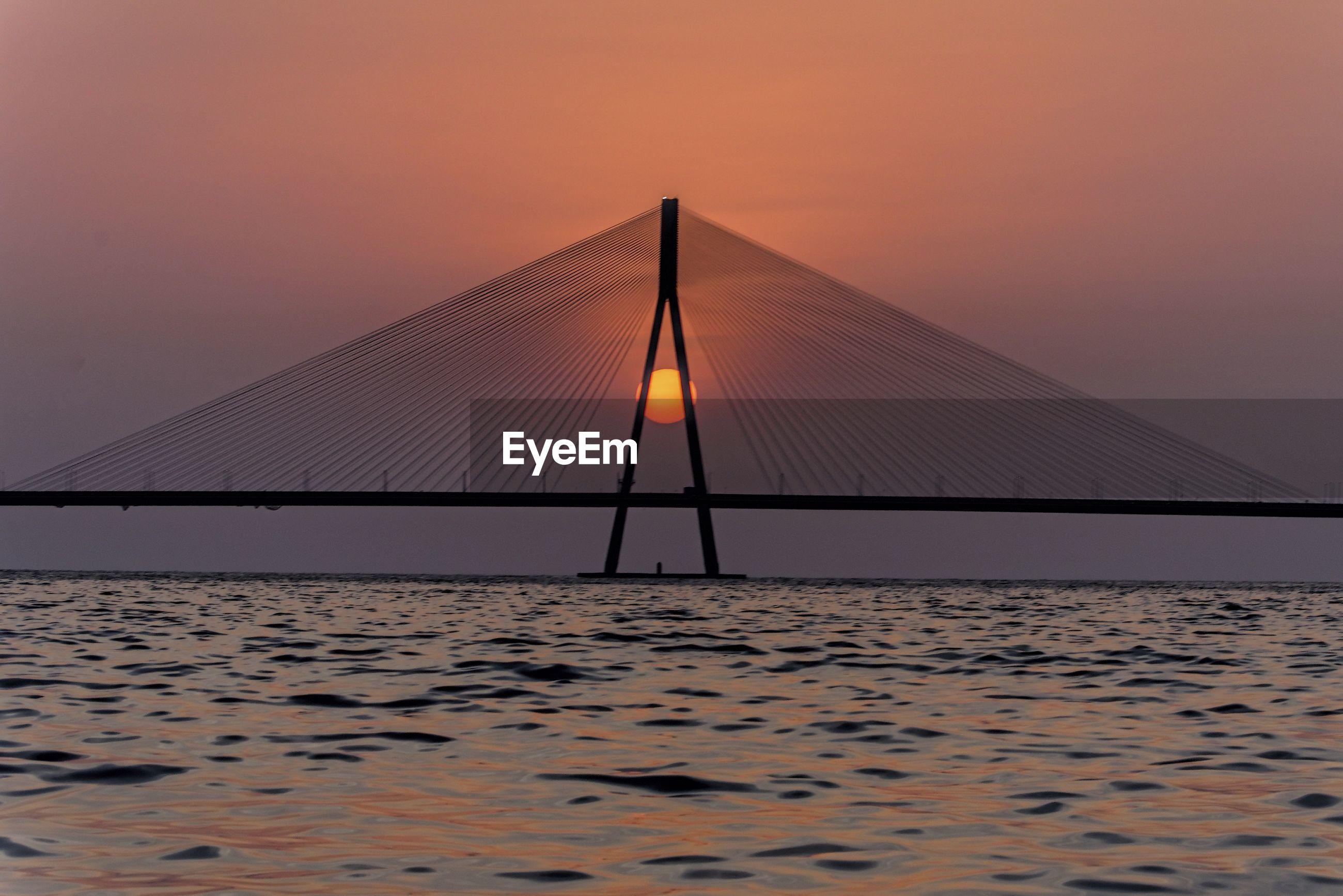 SILHOUETTE BRIDGE BY SEA AGAINST ORANGE SKY