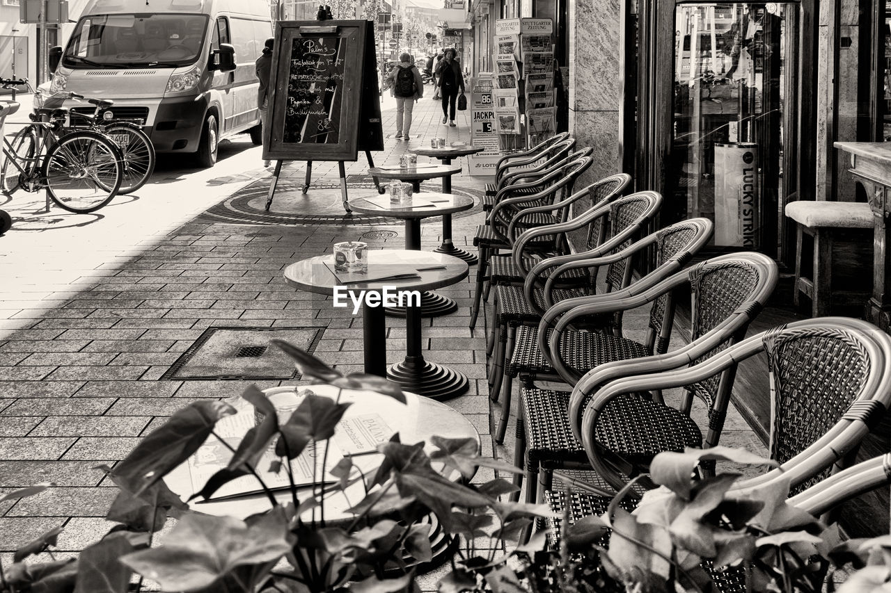 transportation, mode of transportation, street, day, footpath, bicycle, land vehicle, city, sidewalk, no people, building exterior, architecture, outdoors, seat, large group of objects, built structure, business, nature, chair, wheel
