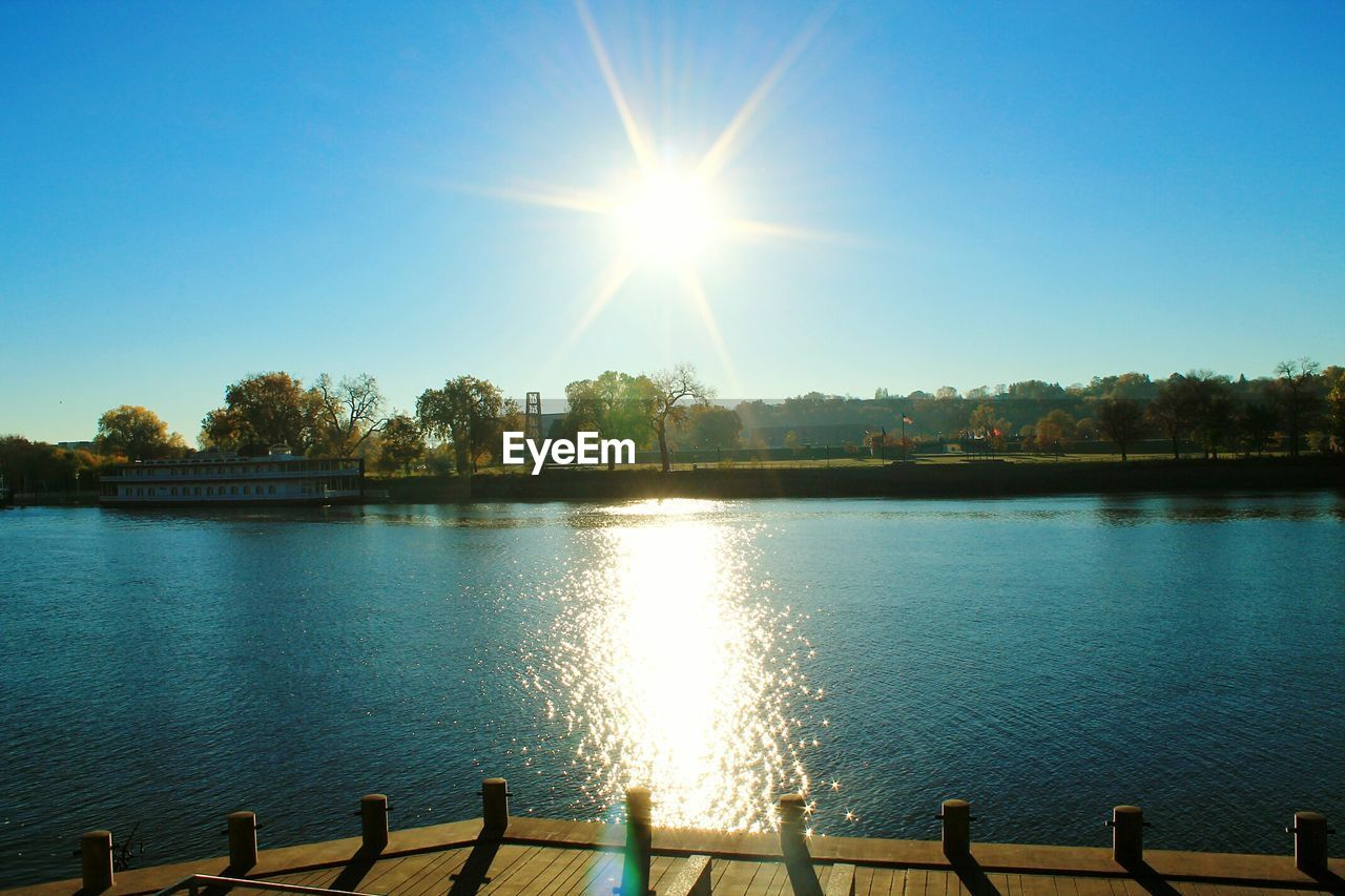 sun, sunlight, sunbeam, lens flare, tree, water, clear sky, sky, nature, lake, no people, outdoors, beauty in nature, scenics, tranquility, day, built structure, architecture