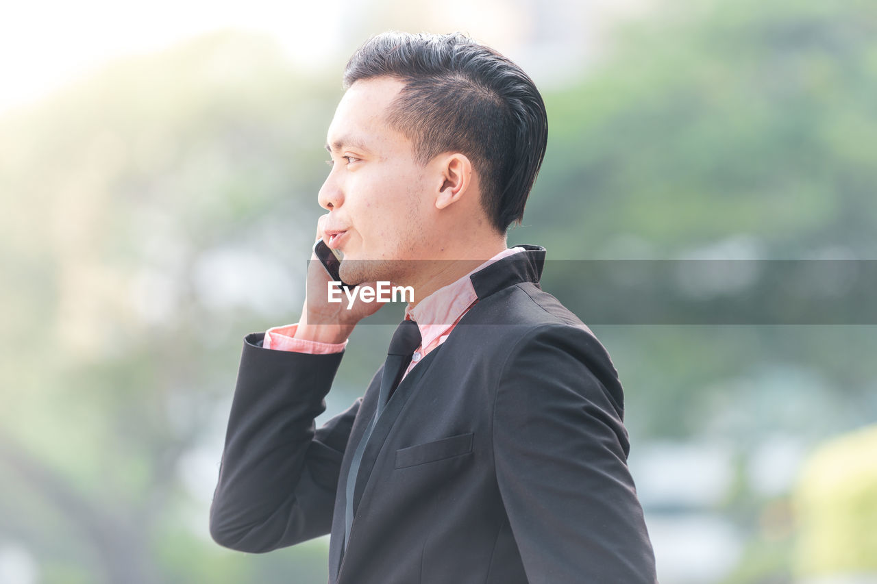 one person, men, businessman, focus on foreground, males, real people, business person, suit, young men, business, well-dressed, young adult, standing, day, looking, corporate business, looking away, occupation, outdoors, menswear