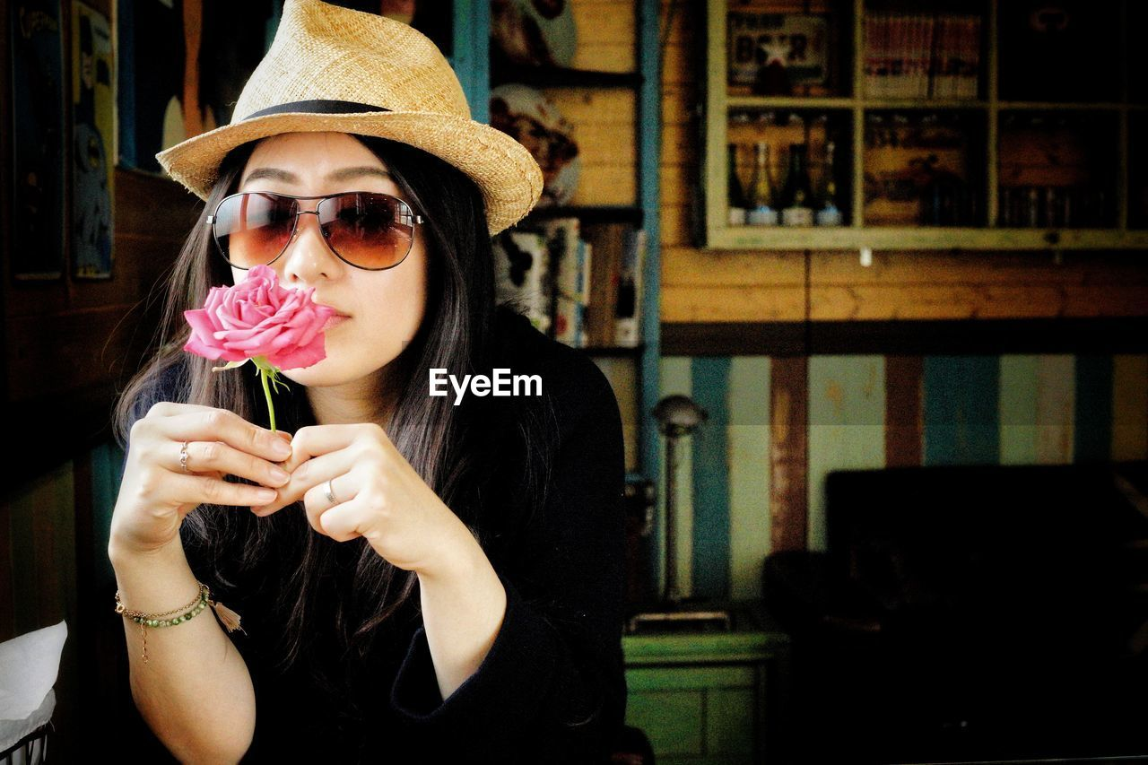 Portrait of woman in sunglasses and hat holding flower at home