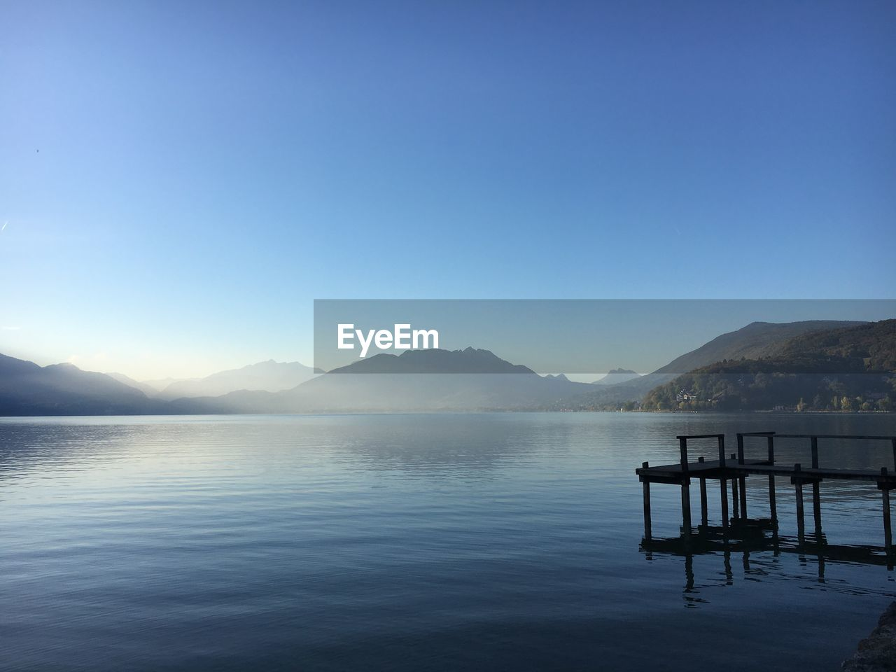 mountain, sky, water, beauty in nature, scenics - nature, tranquility, tranquil scene, lake, clear sky, copy space, mountain range, blue, nature, non-urban scene, waterfront, no people, idyllic, day, reflection, outdoors