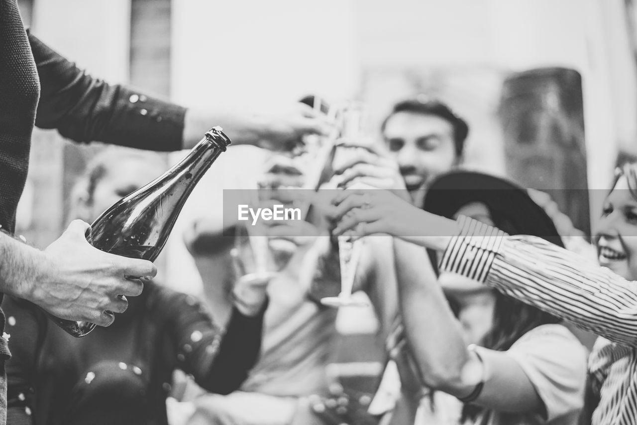 Cheerful Male And Female Friends Toasting Champagne Flutes During Party Outdoors