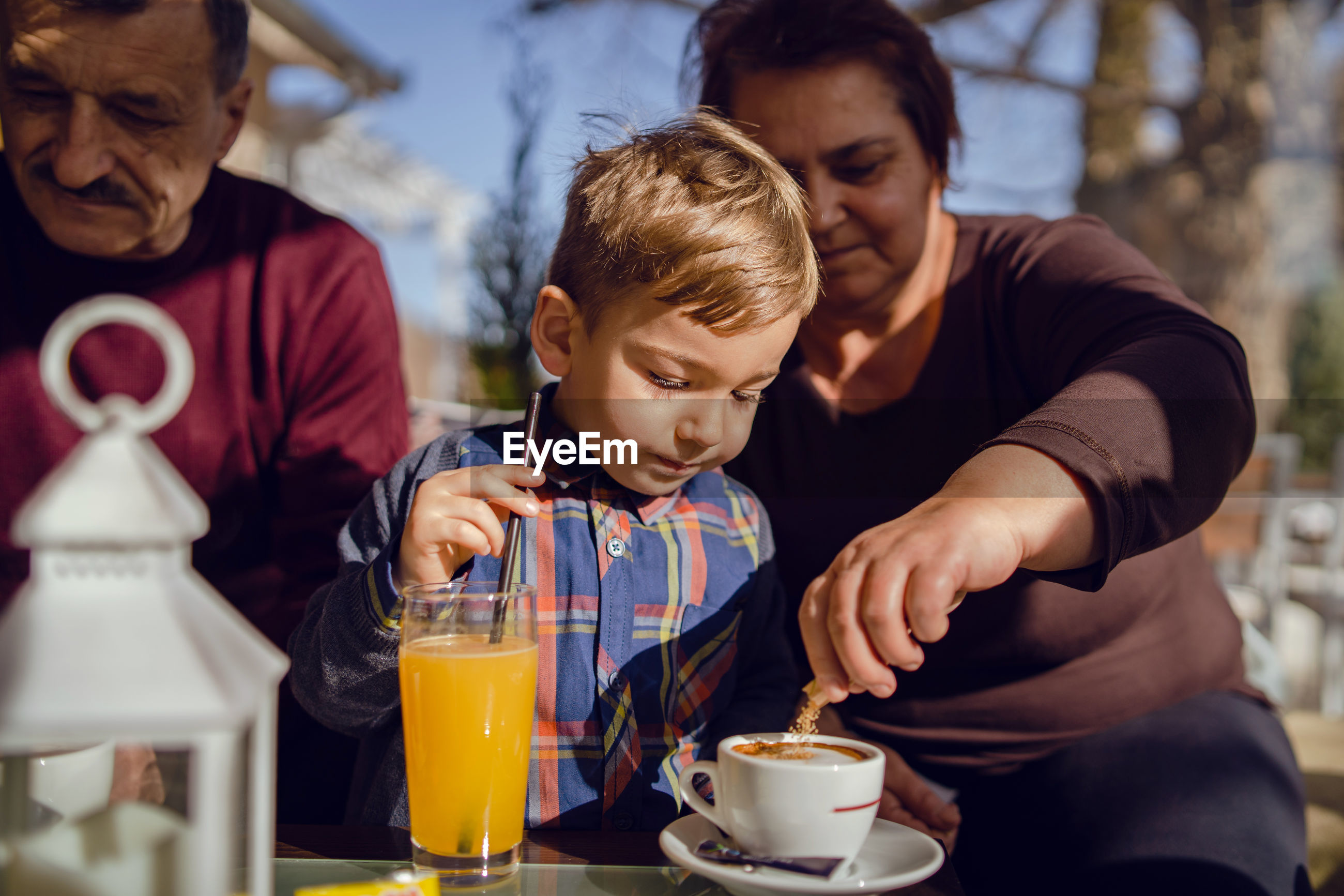 Boy looking at grandmother making coffee on table