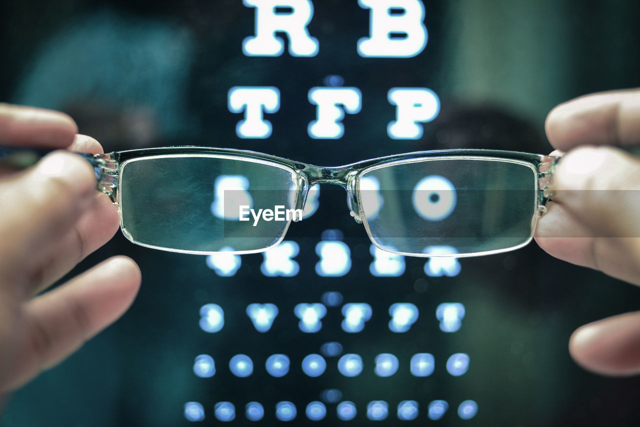Cropped Hands Holding Eyeglasses Against Alphabets