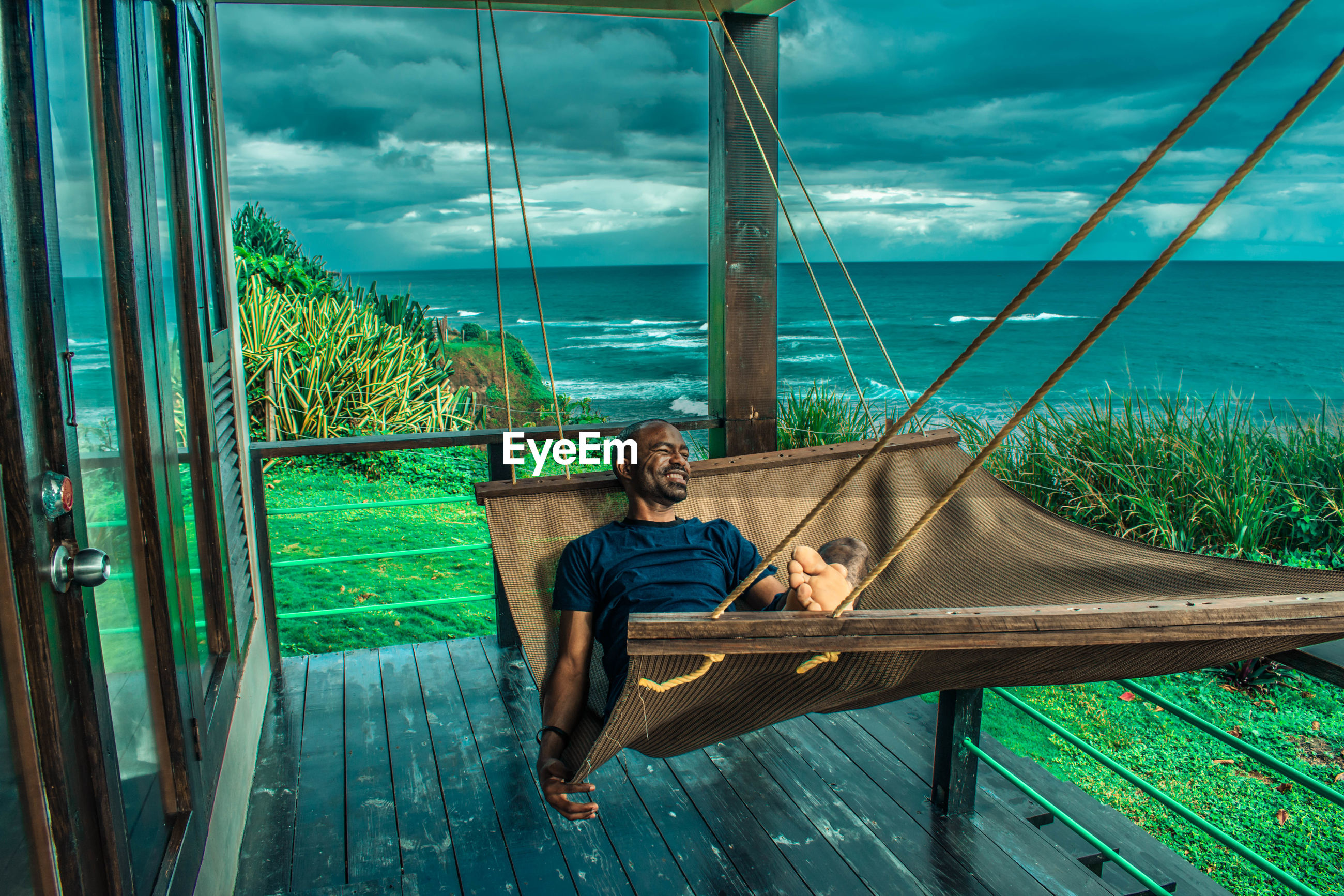 Man relaxing against sea in hammock at porch