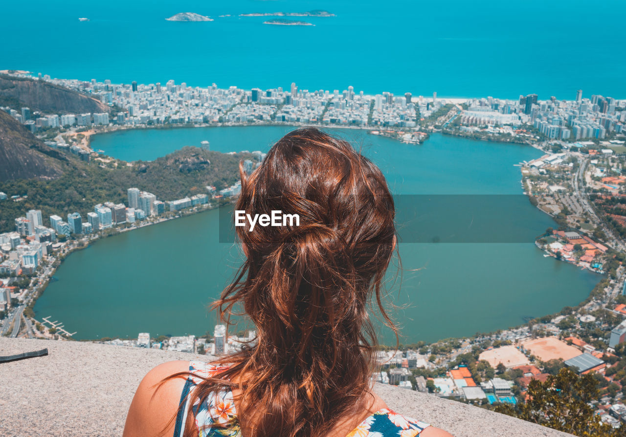 Rear view of woman looking at sea and city