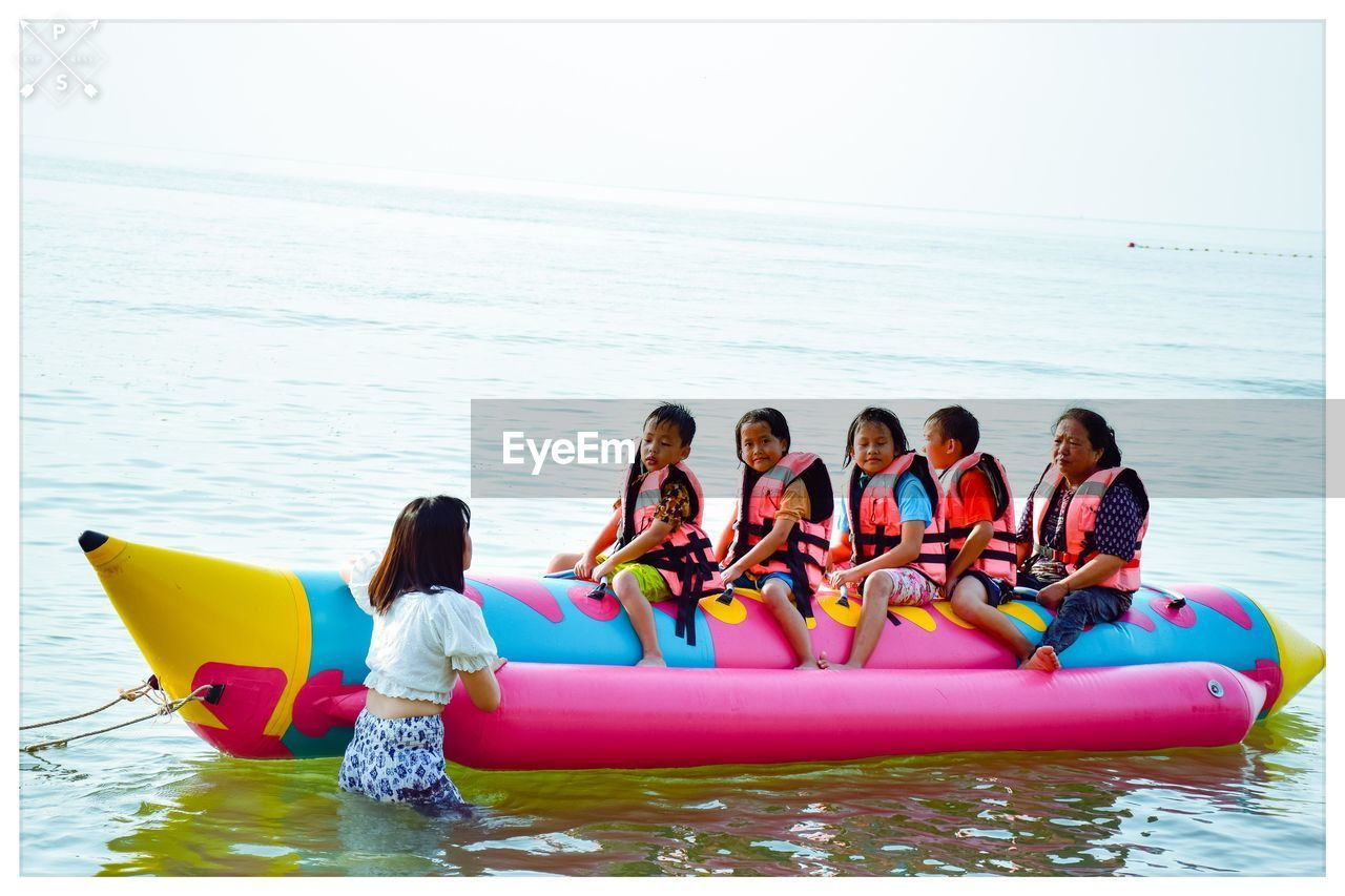 water, sea, childhood, child, group of people, horizon, women, leisure activity, horizon over water, lifestyles, real people, girls, females, day, nature, inflatable, beauty in nature, boys, sky, outdoors, pool raft, sister