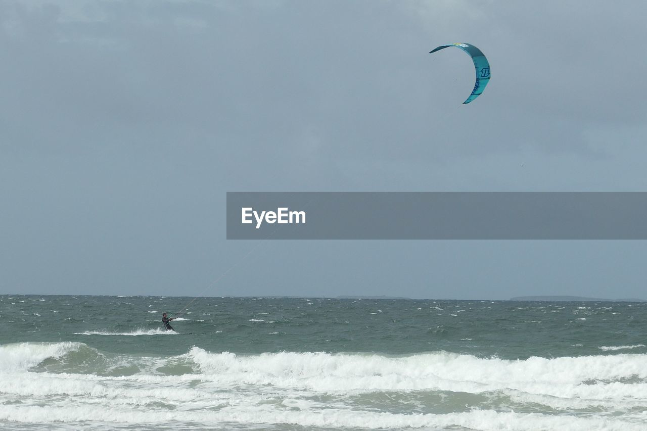 sea, sport, water, adventure, horizon over water, sky, extreme sports, aquatic sport, motion, horizon, surfing, leisure activity, unrecognizable person, wave, real people, kiteboarding, beauty in nature, lifestyles, scenics - nature, freedom, outdoors