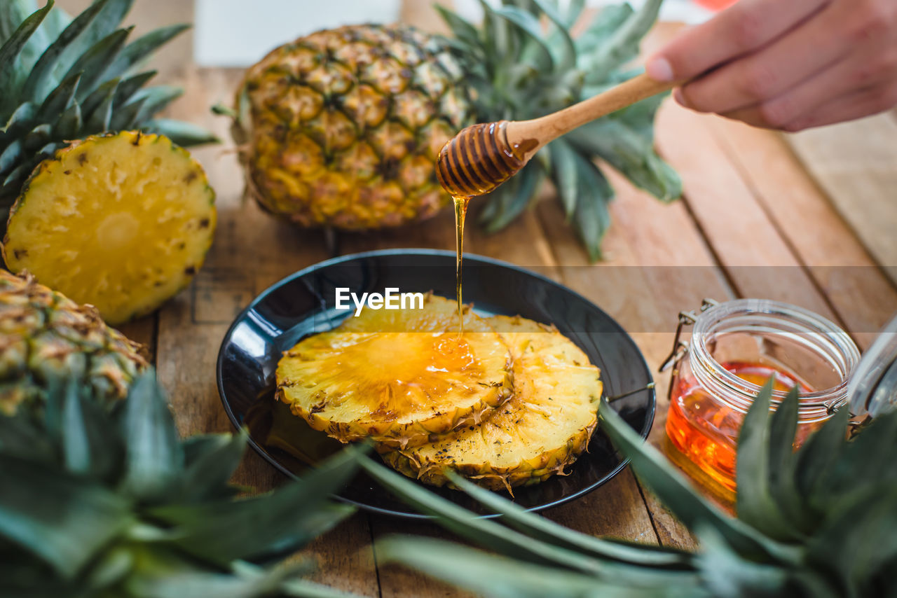 Cropped Hand Pouring Honey On Pineapple Slice