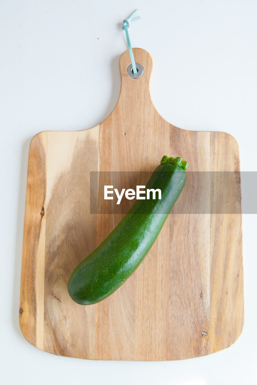 indoors, food and drink, still life, vegetable, freshness, food, green color, wood - material, wellbeing, healthy eating, cutting board, high angle view, table, studio shot, no people, close-up, spice, white background, directly above, pepper