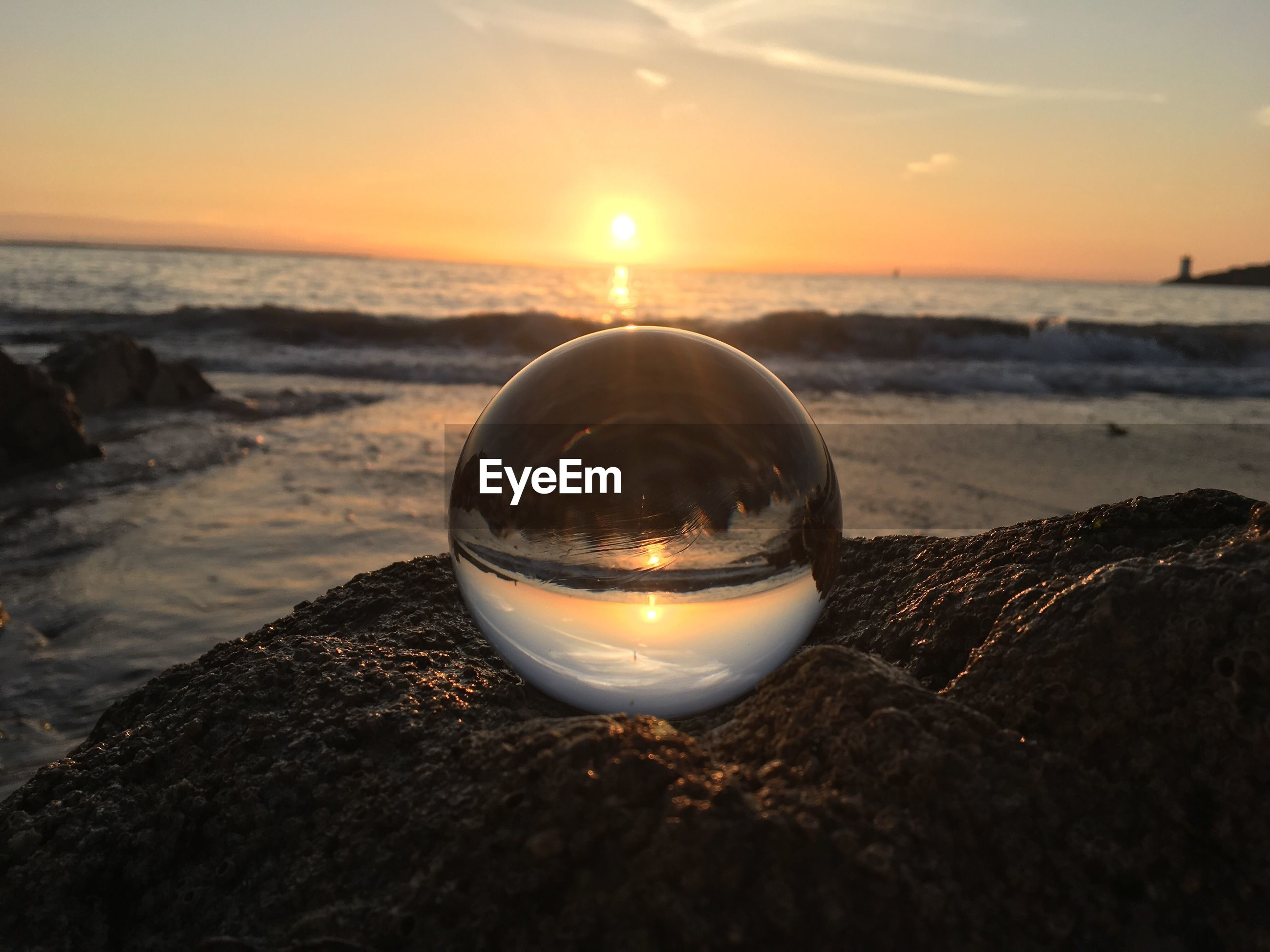 Close-up of crystal ball on rock at beach during sunset