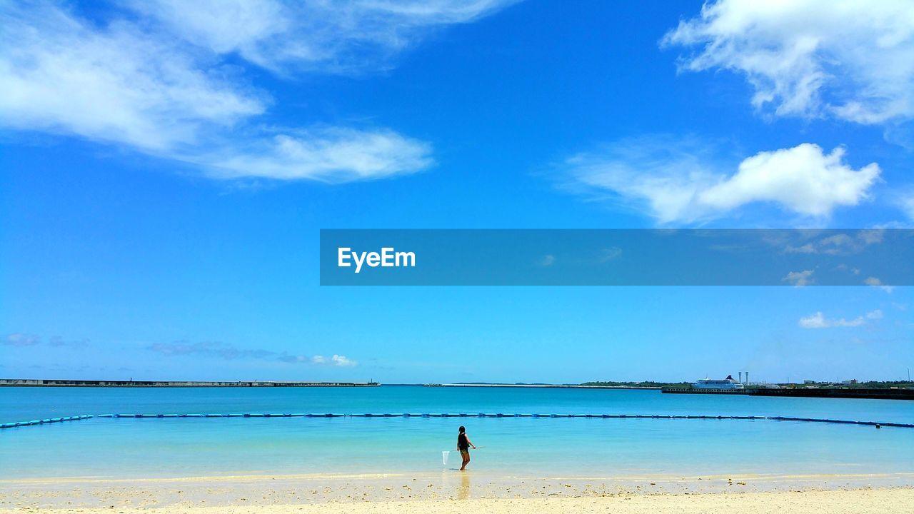 Man at beach against blue sky