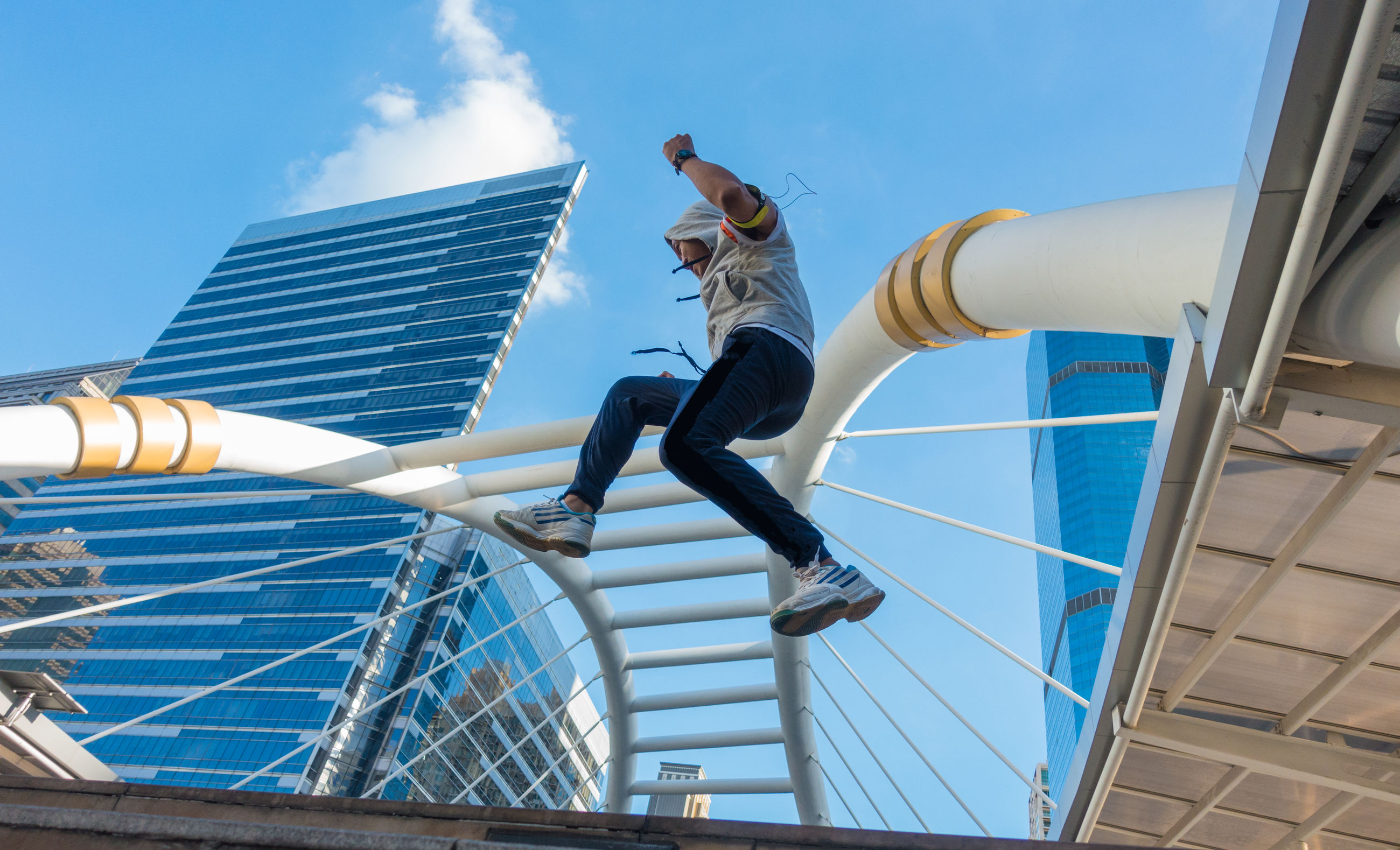Low angle view of man jumping on steps against blue sky