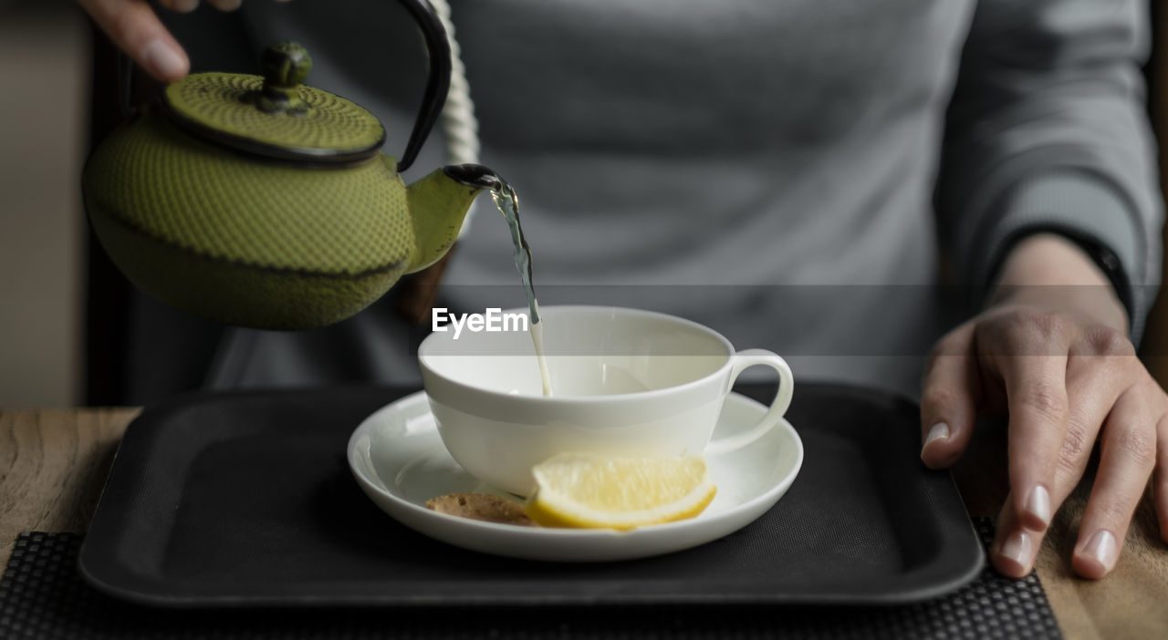 MIDSECTION OF PERSON HAVING TEA