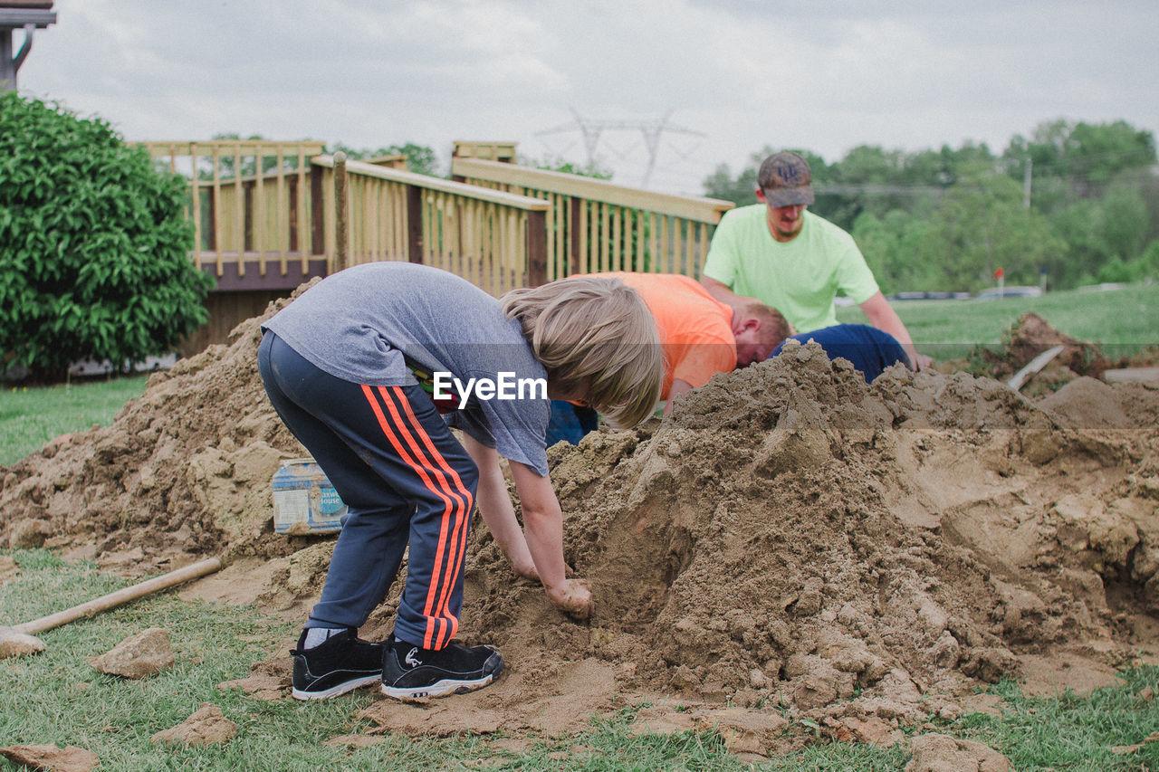 People Digging Mud On Field