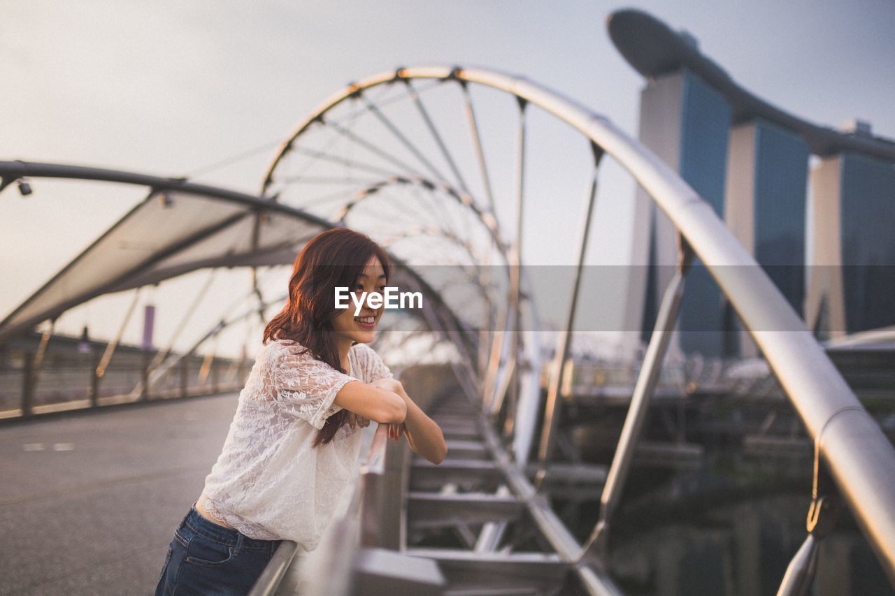 Young Woman On Bridge In City Against Sky