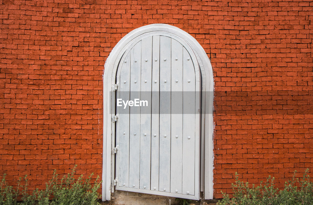 built structure, architecture, brick wall, building exterior, brick, wall, door, wall - building feature, entrance, no people, closed, day, building, security, safety, arch, pattern, wood - material, red, outdoors