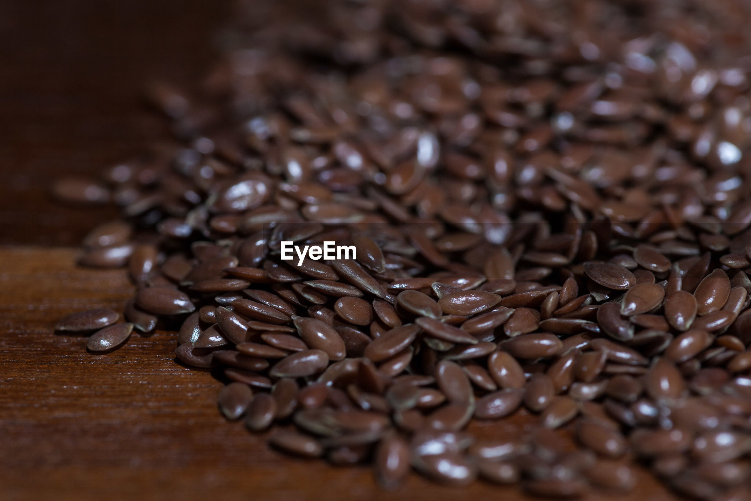 CLOSE-UP OF COFFEE BEANS AND TABLE ON GLASS