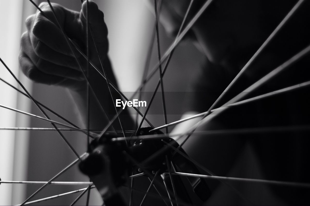 Cropped Image Of Man Seen Through Bicycle Spokes