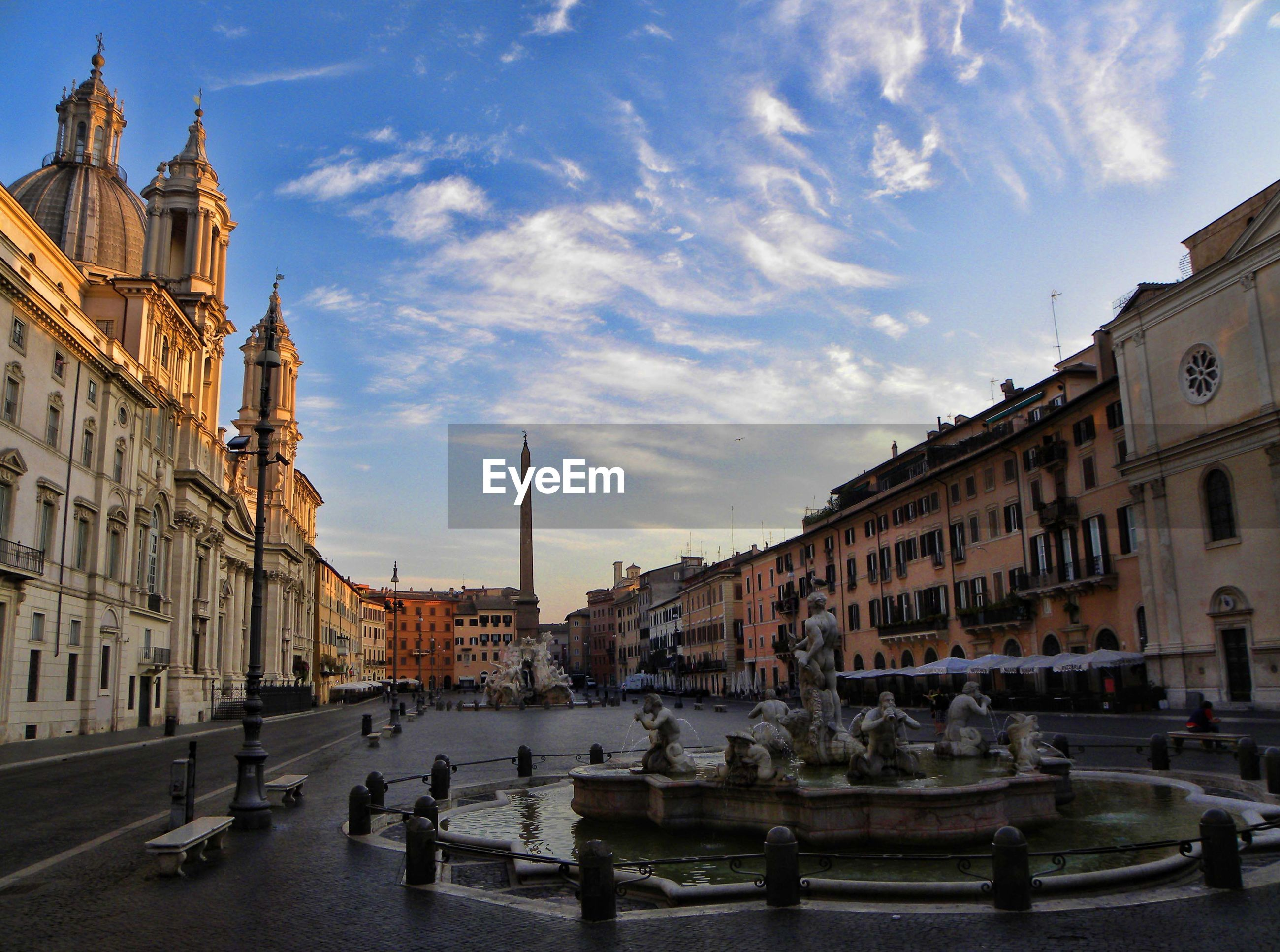 Sculptures in fountain amidst buildings against sky at piazza navona