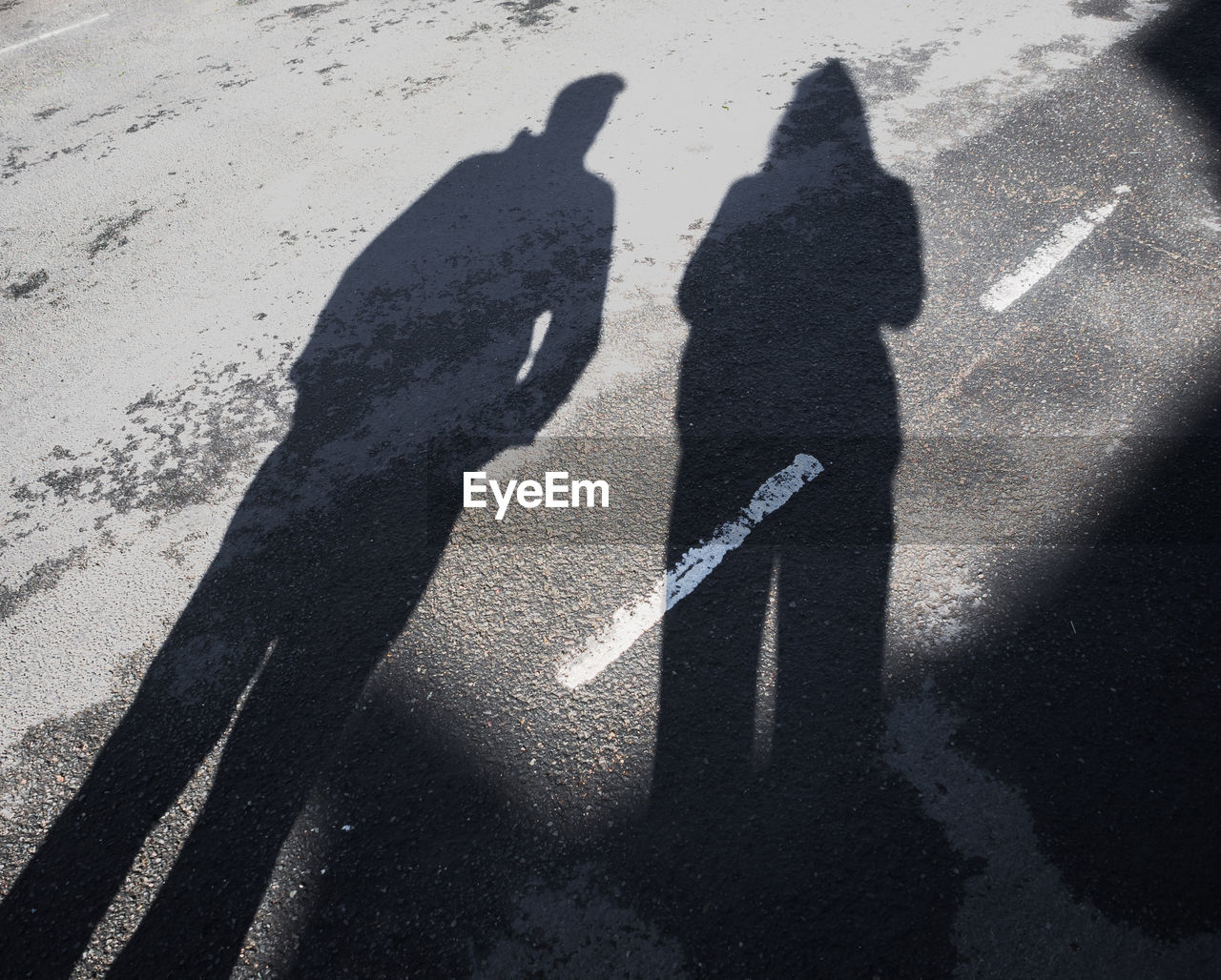 Shadow Of Man And Woman Standing On Road