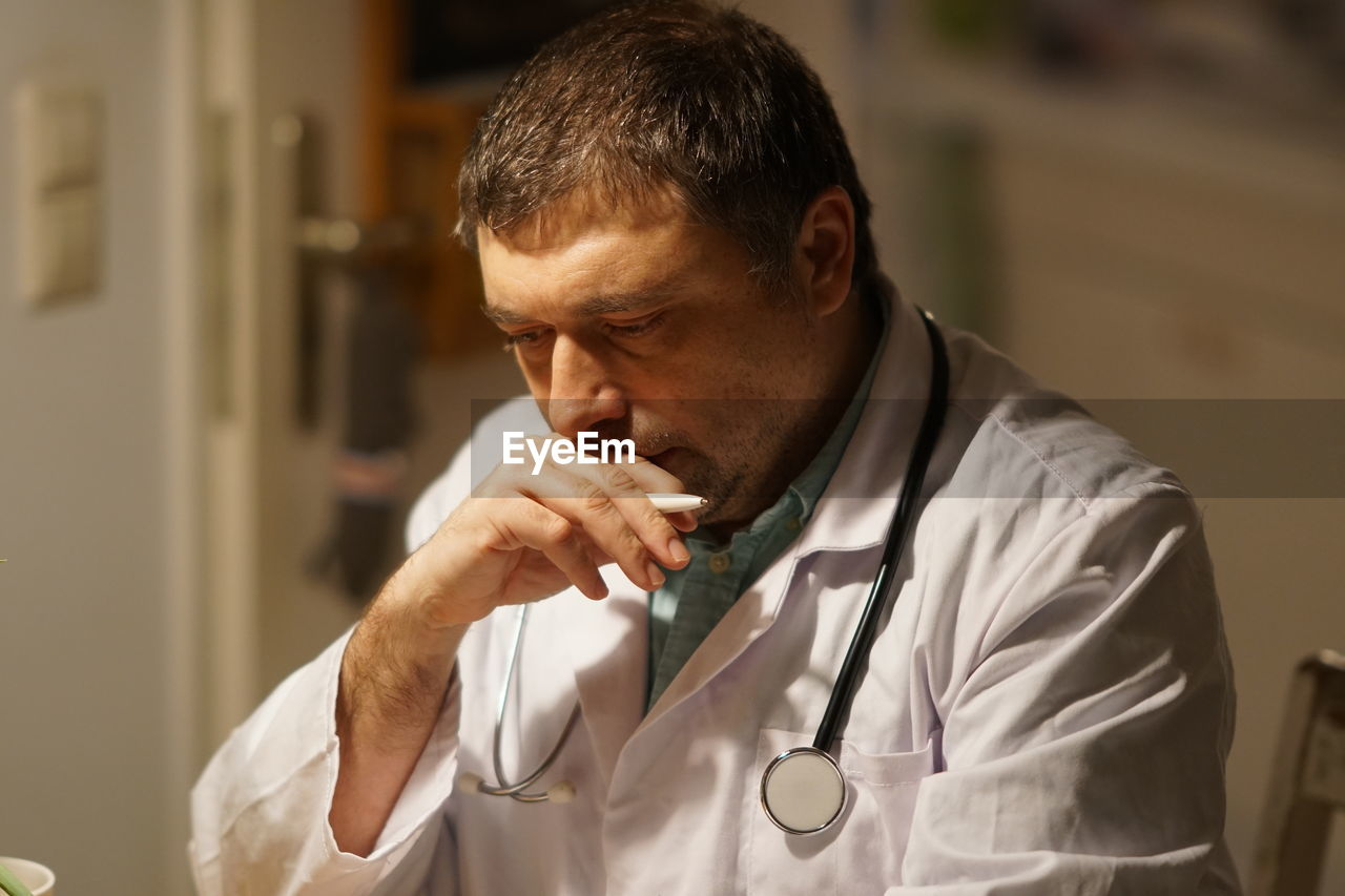 Thoughtful Mature Doctor With Pen Working In Hospital