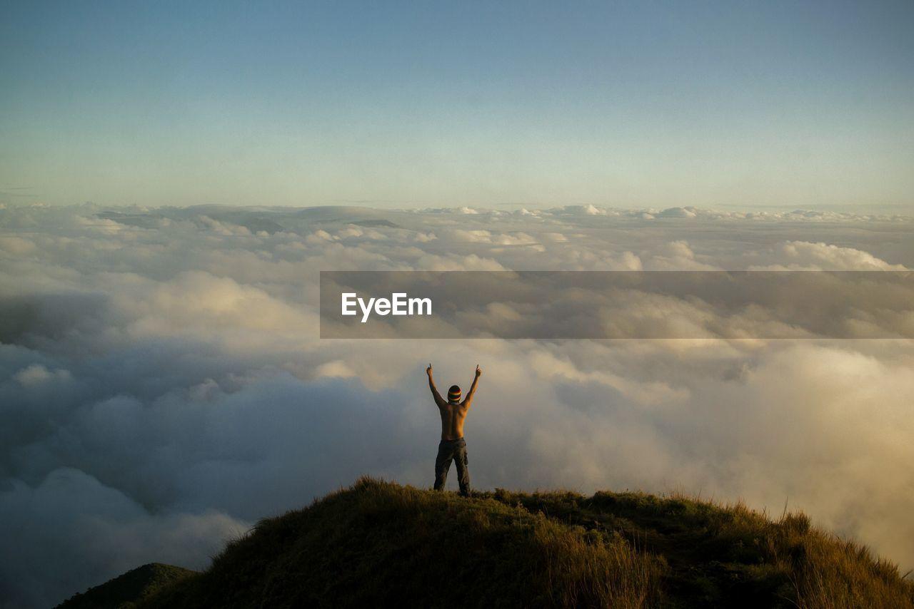 Rear View Of Man On Mountain Peak Against Sky