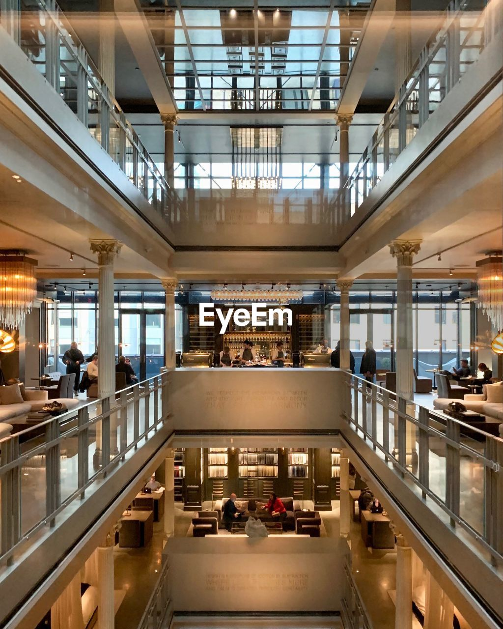 indoors, architecture, illuminated, group of people, shopping mall, lifestyles, modern, real people, crowd, large group of people, railing, table, incidental people, men, high angle view, ceiling, lighting equipment, women, seat, consumerism, luxury